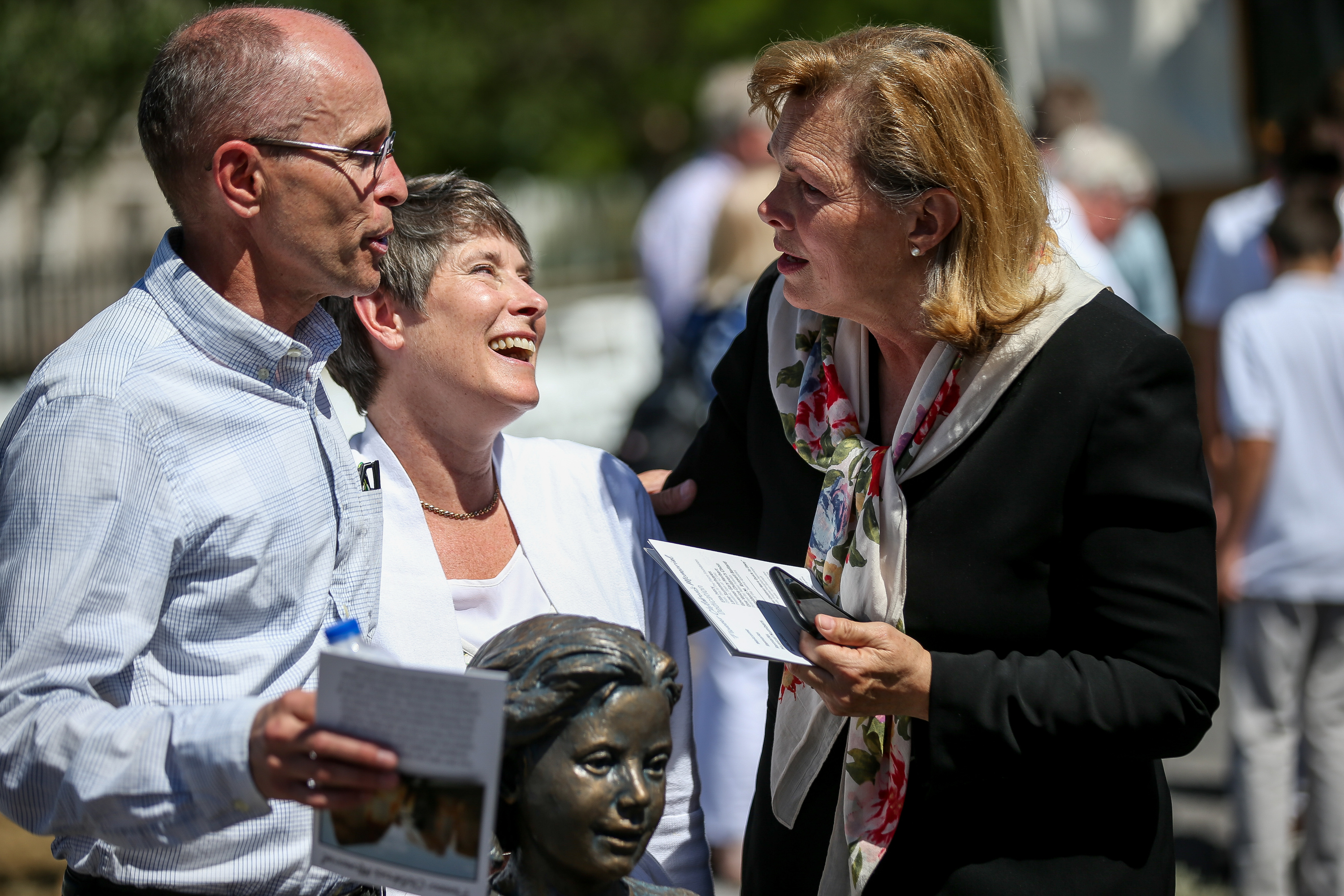 Sculptors Roger and Stefanie Hunt chat with Debbie Christiansen after the dedication of the Children's Pioneer Memorial at This Is the Place Heritage Park in Salt Lake City on Saturday, July 20, 2019.