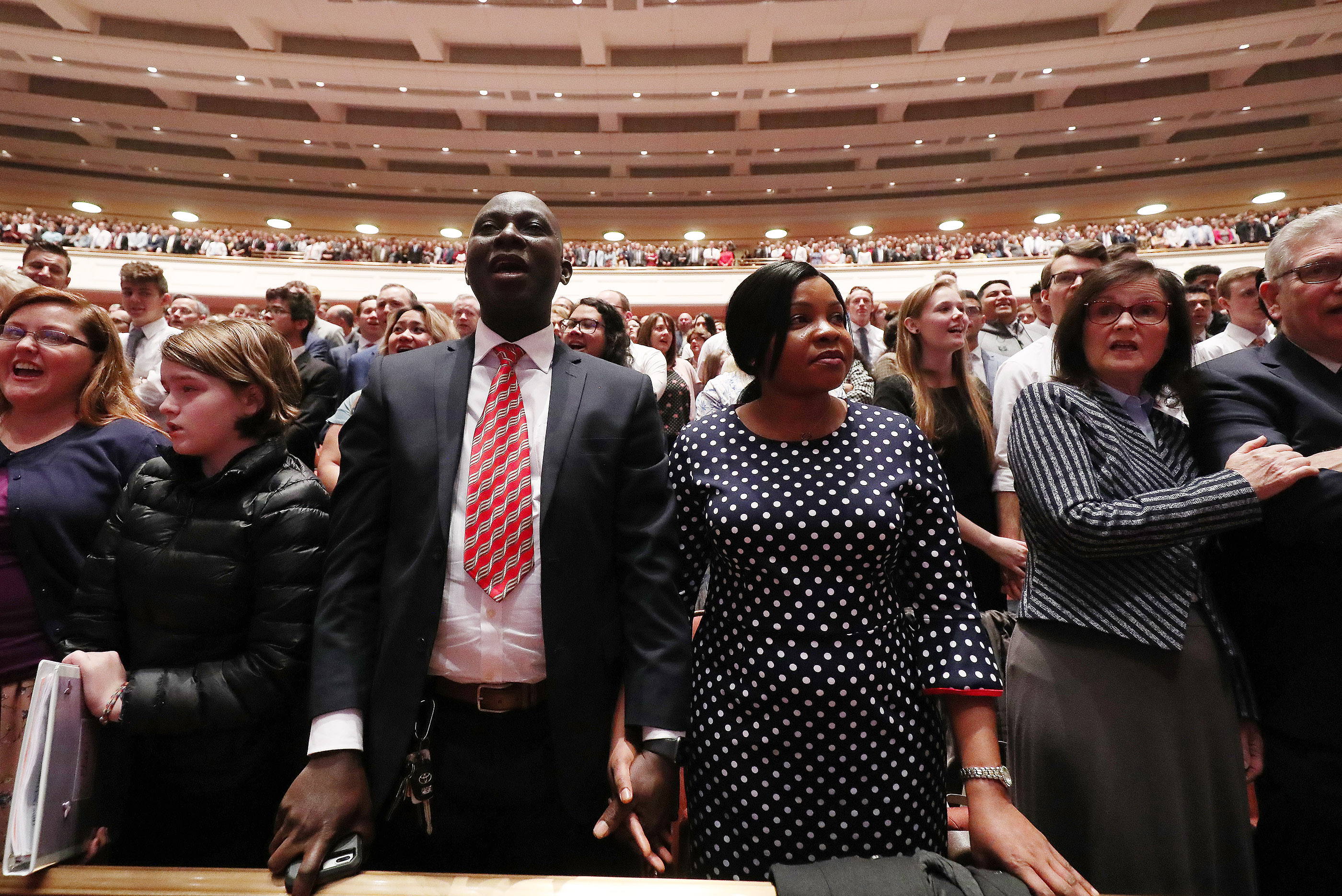 Matthew and Mary Evuarherhe sing a congregational hymn during the 189th Annual General Conference of The Church of Jesus Christ of Latter-day Saints in Salt Lake City on Saturday, April 6, 2019.