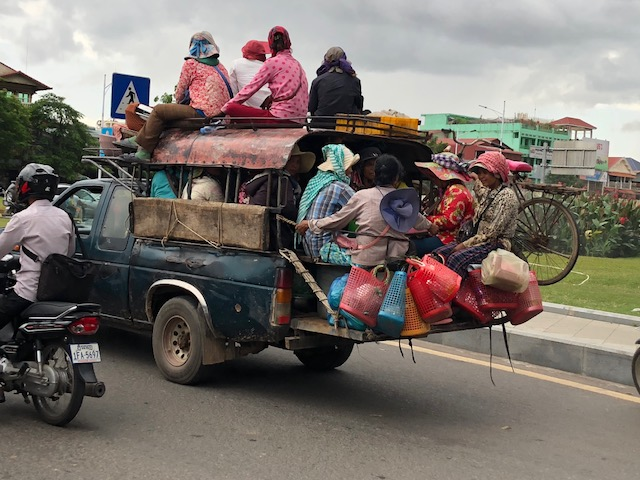 A typical scene of a team effort transporting workers and various goods through the countryside.
