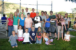 Ralph Olson and his wife, Sharon, are surrounded by fans and family members who showed up to cheer him on as he played in a Church softball game.