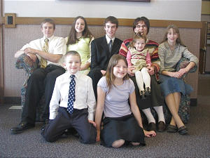 When Capt. Aaron Cheadle was deployed to Iraq last July, he left behind his wife, Laura, back second from right, holding daughter, Rebecca, and children, clockwise from back left, Jacob, Rachel, Joseph, Sariah, Ruth and Samuel.