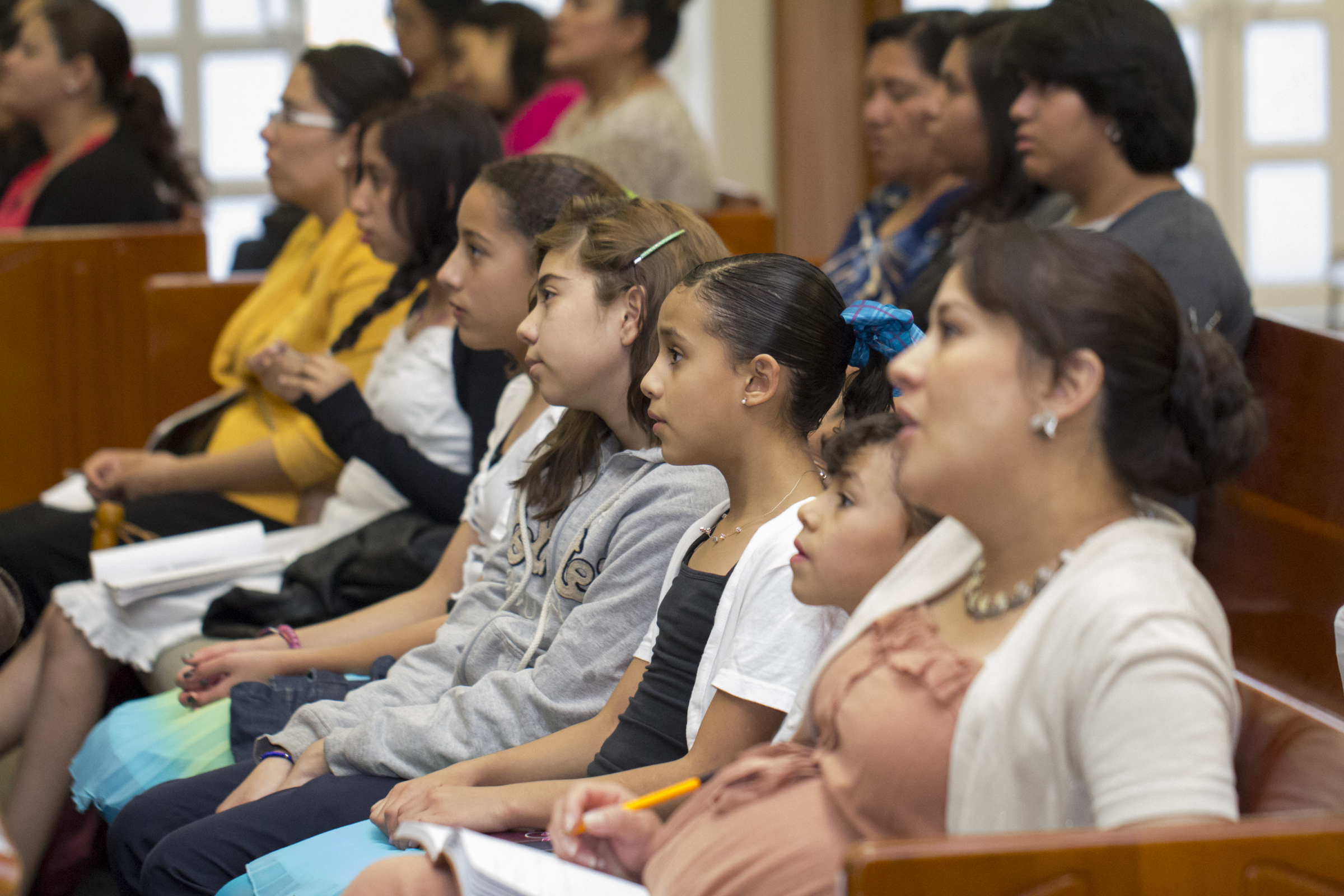 A row of women watch the broadcast of the general women's session of general conference in their local meetinghouse.