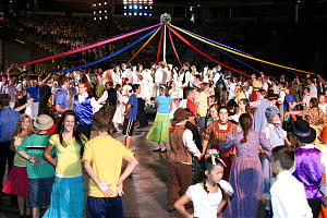 """Youth dance around a maypole during the opening scene - """"Gold Rush Fair"""" - of cultural celebration."""