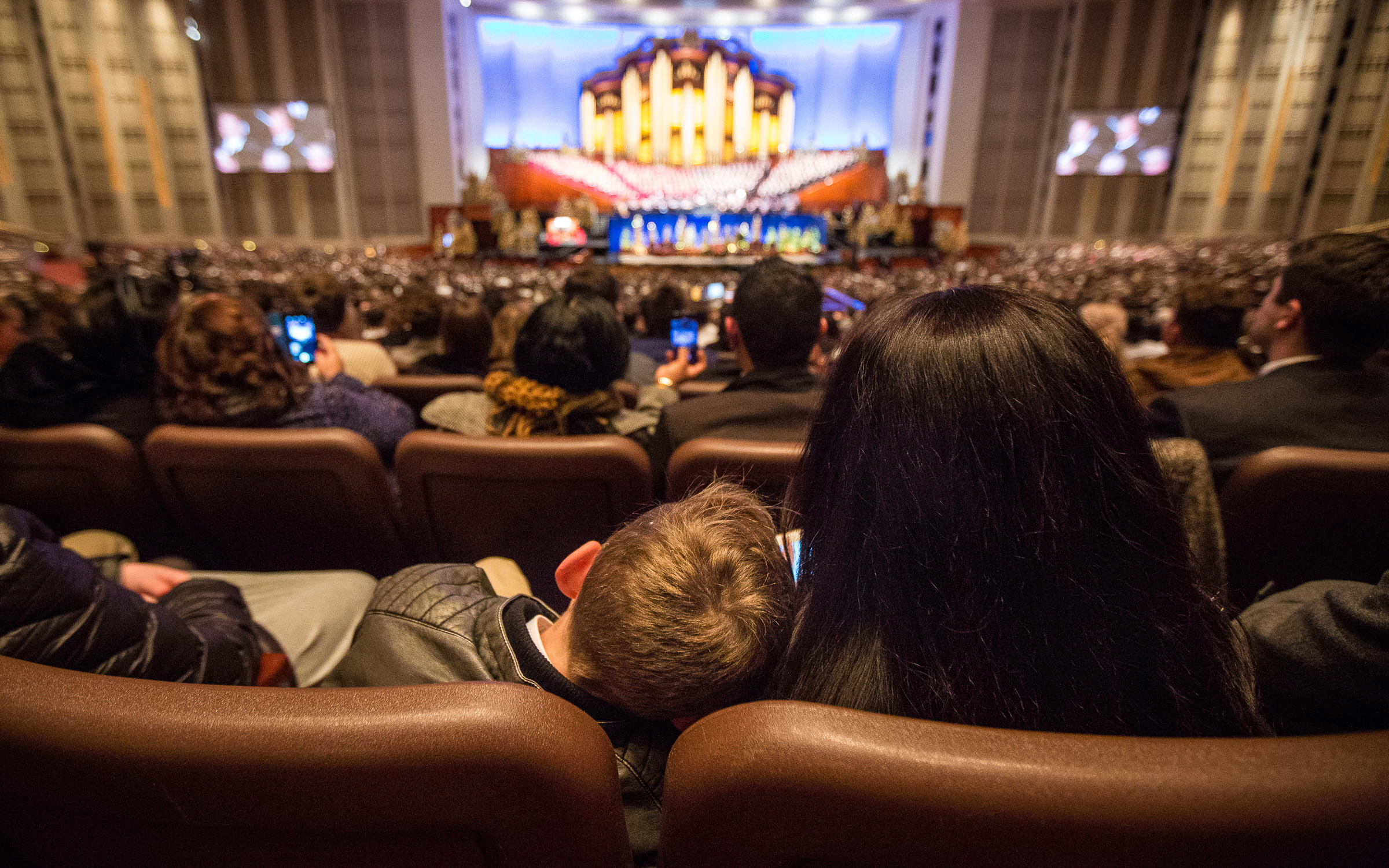 A mother and her son listen as Elder Gary E. Stevenson, a member of the Quorum of the Twelve Apostles, speaks at the First Presidency's Christmas Devotional in the Conference Center in Salt Lake City on Sunday, Dec. 2, 2018.
