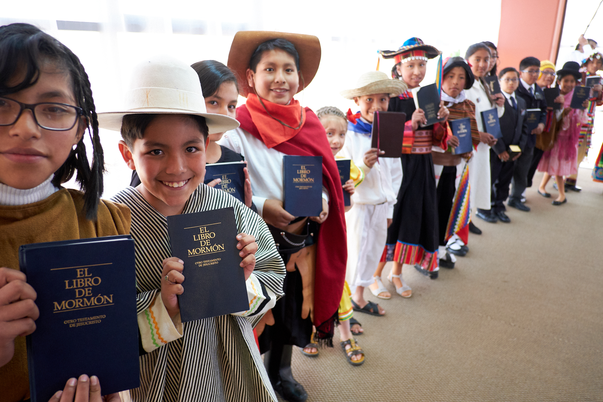Latter-day Saint children line up in the Polideportivo Heroes de Octobre in El Alto, Bolivia, to show President Russell M. Nelson their copies of the Book of Mormon in Spanish.