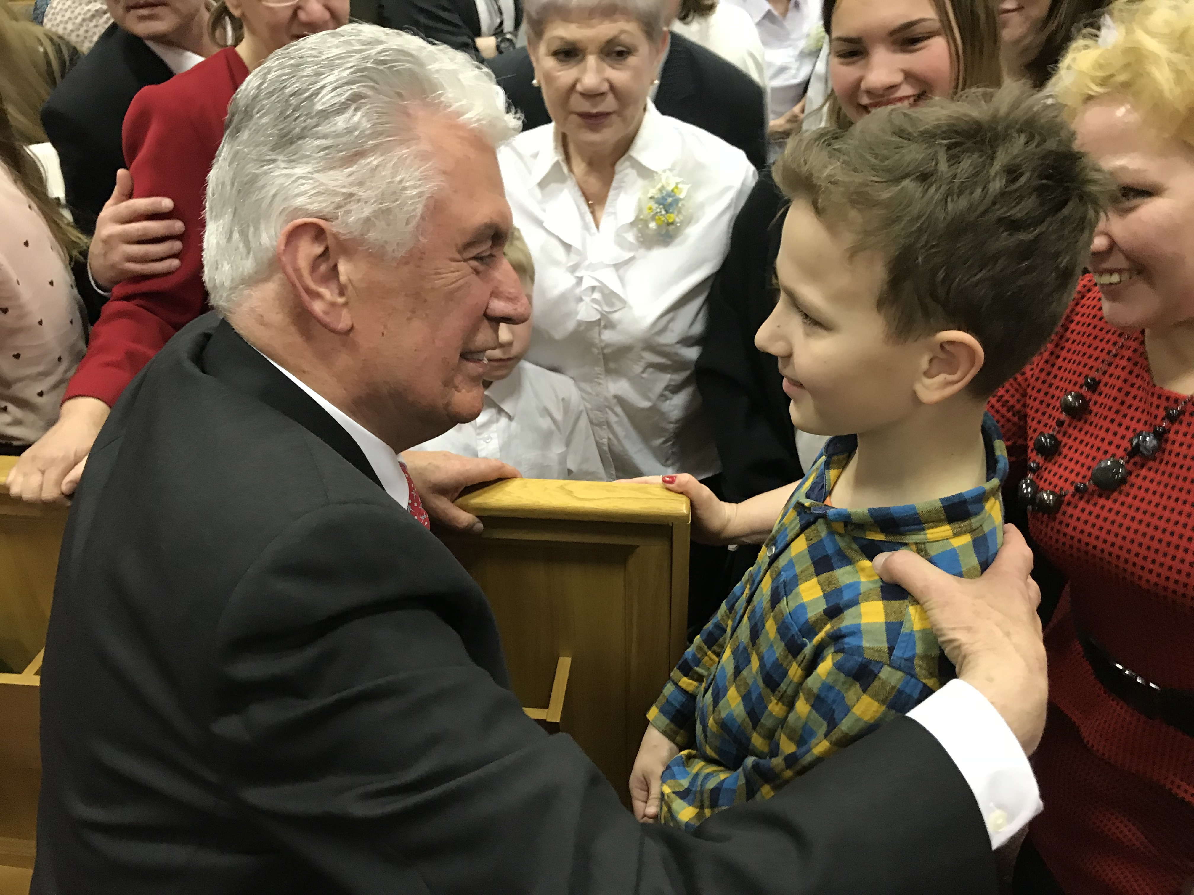 Elder Dieter F. Uchtdorf speaks to a young boy following a member devotional in St. Petersburg, Russia, on April 26, 2018.
