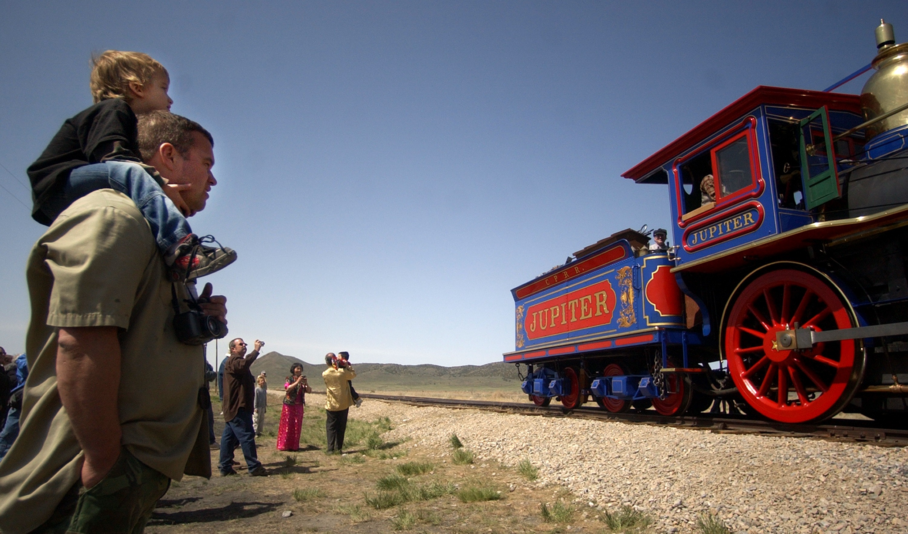 Stuart Taylor and his son Jacob join other spectators at the 139th annual golden spike celebration in Promontory Summit, Utah, on Saturday, May 10, 2008, as the wood-fired Jupiter engine rolls toward the point of where the driving of the last spike is reenacted each year.