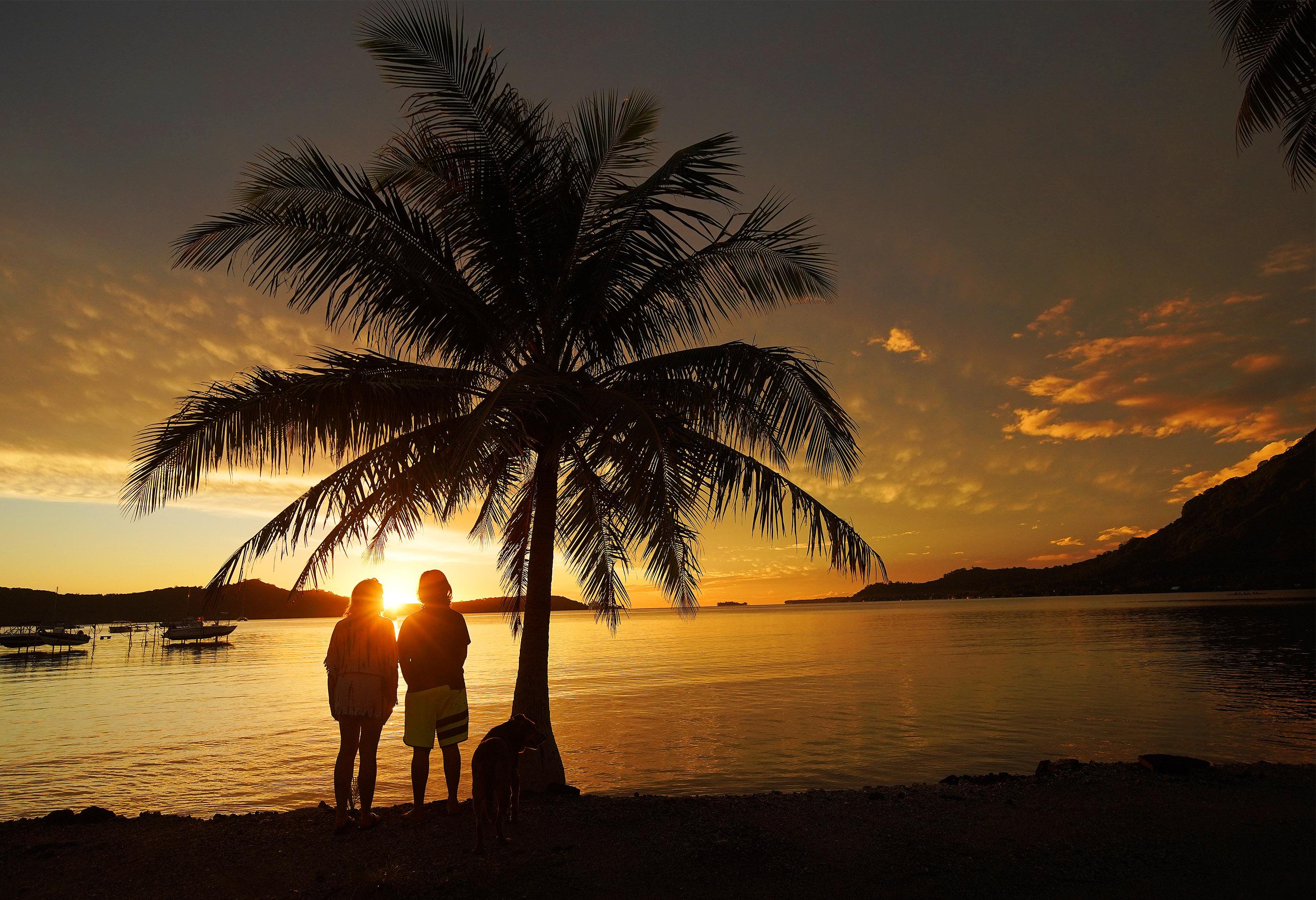 A couple watch the setting sun in Bora Bora on May 28, 2019.