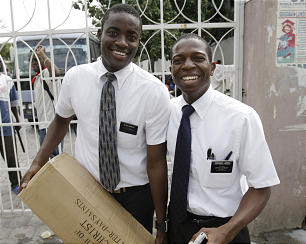 Mission President Kellin Joseph, right, and Elder Sterrin Dumelus pause for a moment while helping Haitians in Prince Au Port, Haiti.