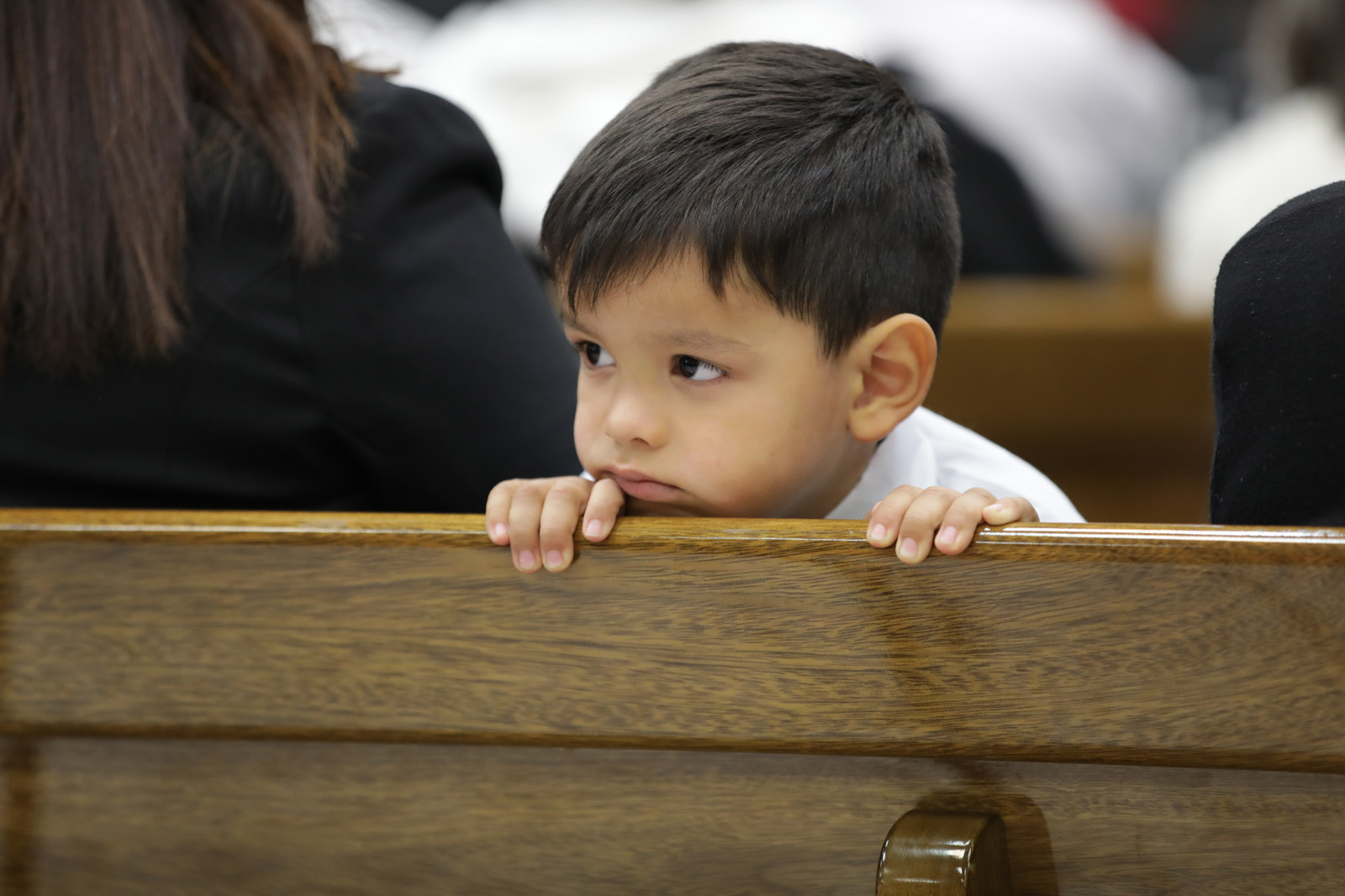 A young boy sits near his family while attending a member meeting in the Rio Gallegos District in Argentina where Elder Dale G. Renlund of the Quorum of the Twelve Apostles spoke on Feb. 21, 2019.
