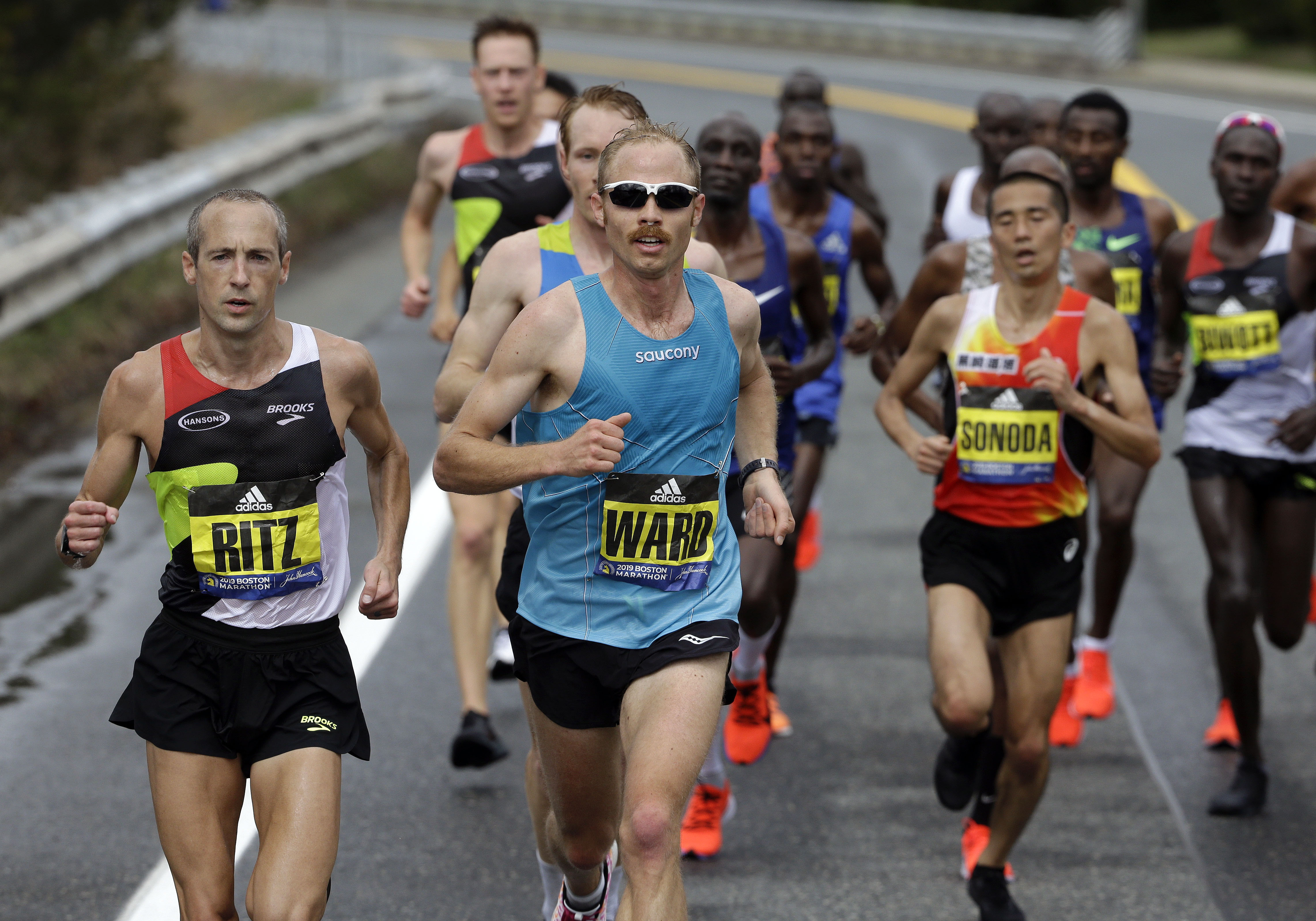 Jared Ward, center, of Mapleton, Utah, leads the pack in front of Dathan Ritzenhein, left, of Belmont, Mich., and Hayato Sonoda, right, of Japan, as they run the course during he 123rd Boston Marathon on Monday, April 15, 2019, in Natick, Mass. (AP Photo/Steven Senne)