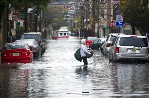 A resident walks through flood water and past a stalled ambulance in the aftermath of superstorm Sandy on Tuesday, Oct. 30, in Hoboken, NJ.