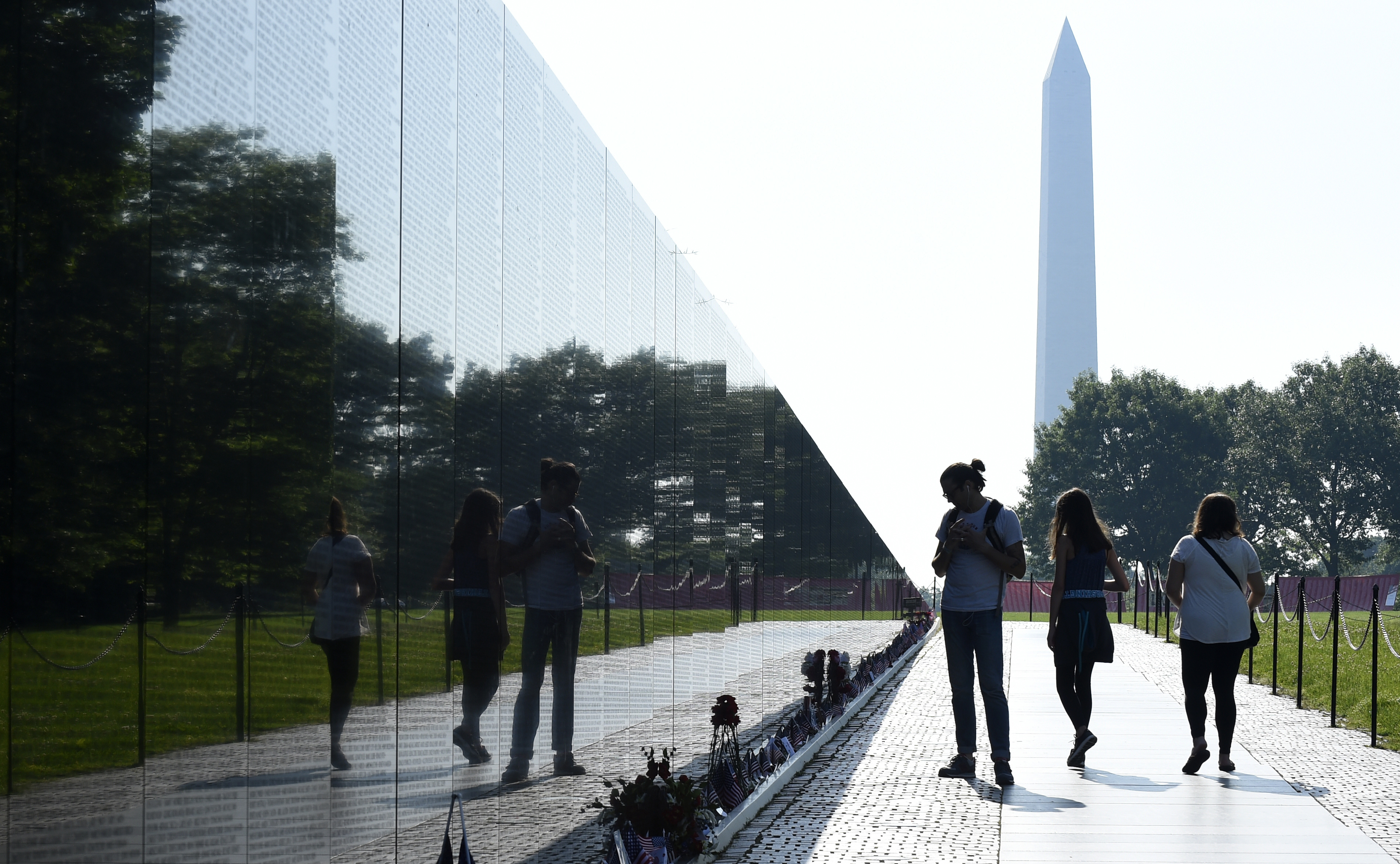 The Washington Monument is seen in the background as people visit the Vietnam Memorial in Washington, Friday, May 27, 2016, on the stat of the Memorial Day weekend. (AP Photo/Susan Walsh)