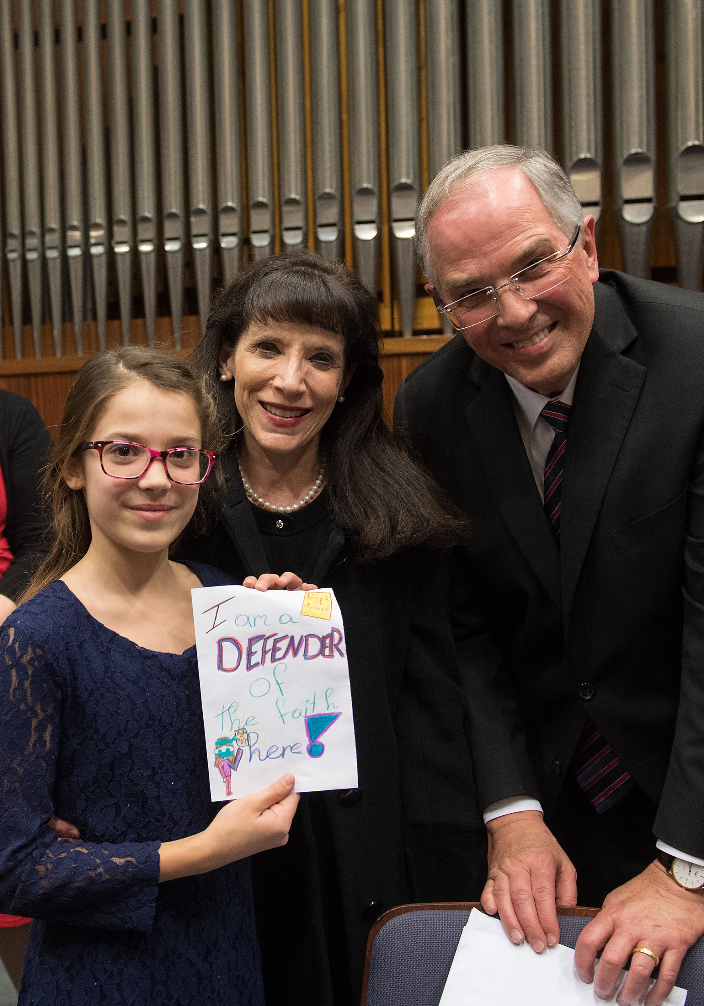 """Elder Neil L. Andersen and Sister Kathy Andersen talk with a young girl after a meeting with the members in Vienna. The young girl had made a sign during the meeting that read, """"I am a defender of the faith."""""""