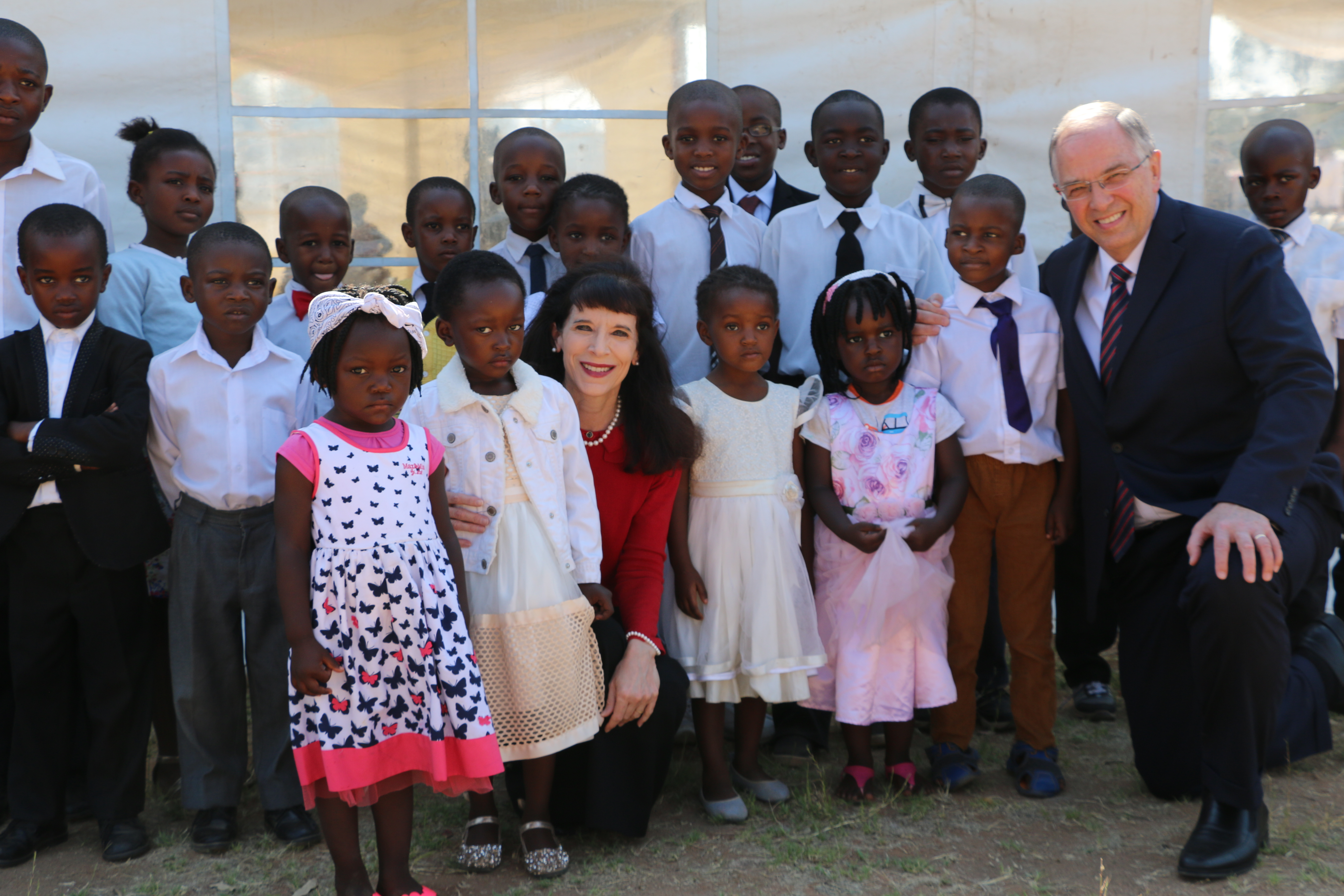 Elder Neil L. Andersen of the Quorum of the Twelve Apostles, center with Sister Kathy Andersen gather with children after a member meeting in Zimbabwe on Nov. 18. 2018.