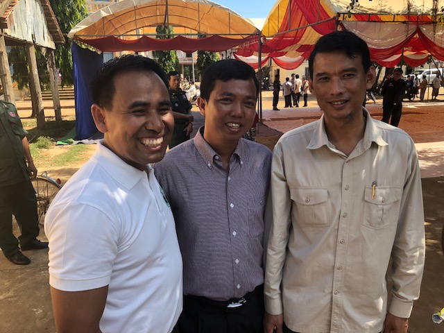 Samnang Sea (left) stands with two of the government officials with whom he worked closely to coordinates the efforts of the Church and LDS Charities for the distribution of the food — the director of Cults & Religion for the Kampong Cham province and the district governor.