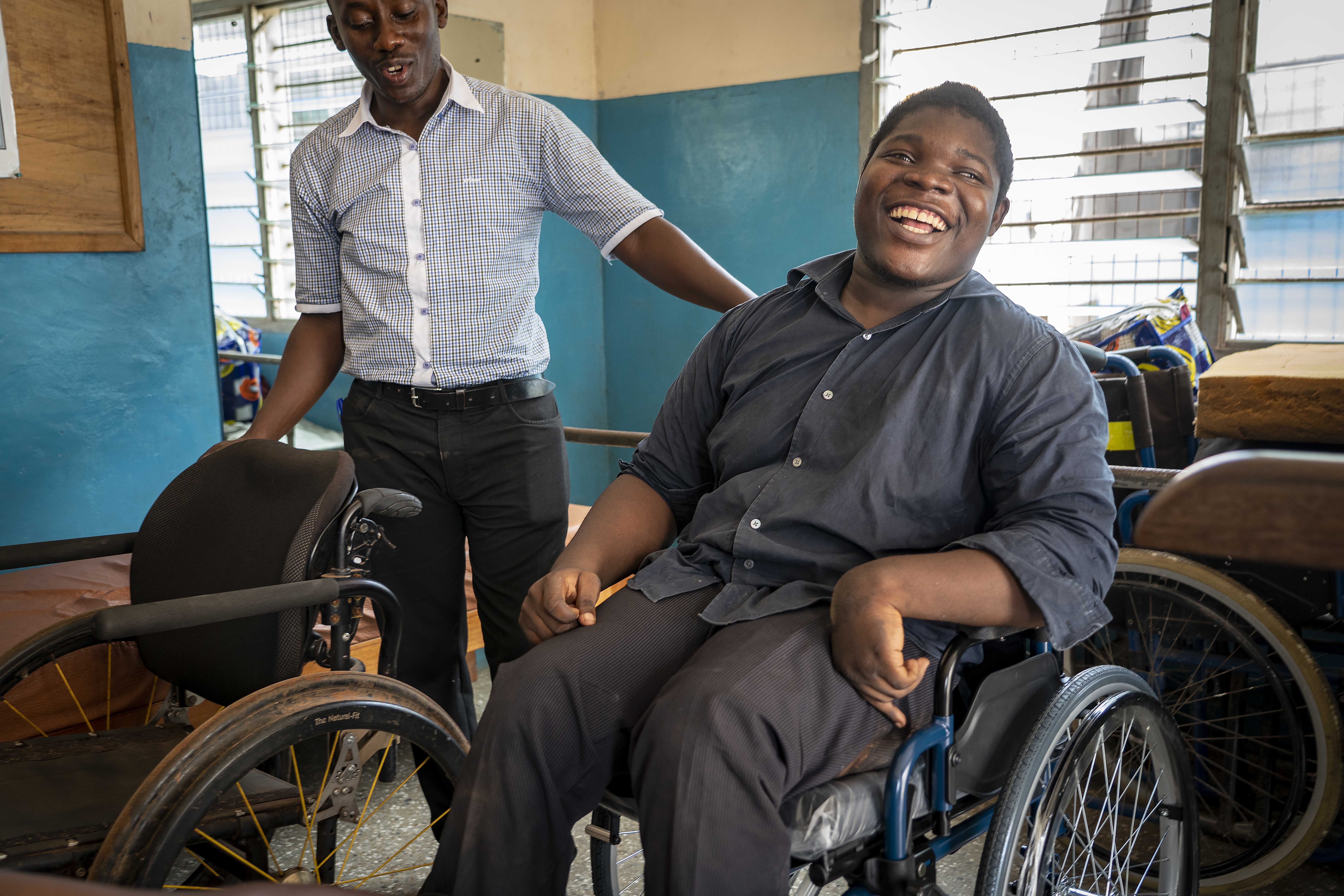 A young man in Ghana is fitted with a wheelchair with help from an LDS Charities technician.