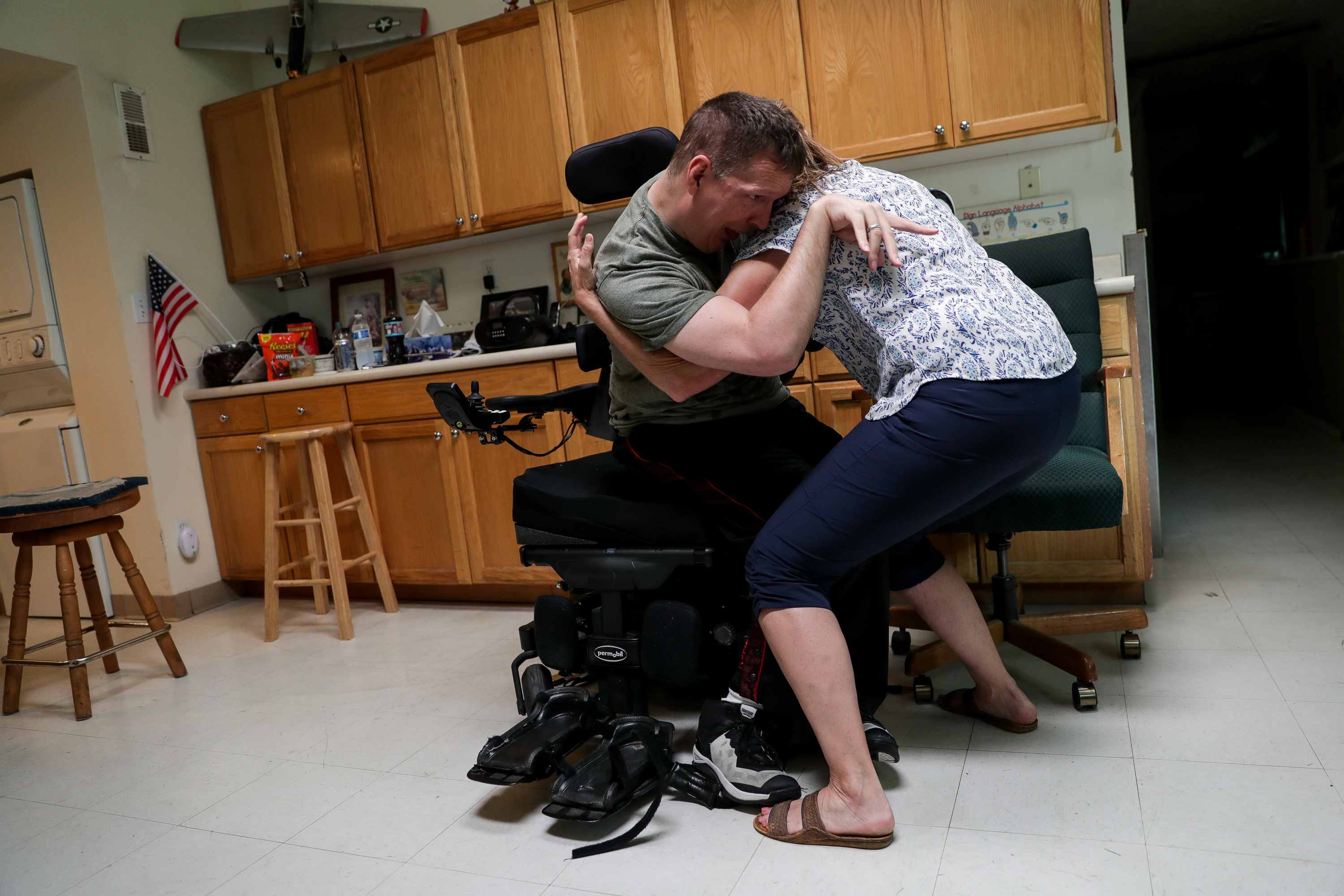 Orin Voorheis is helped up out of his motorized wheelchair by his caregiver Wendy Tobey at his home in Pleasant Grove, Utah, on Tuesday, July 10, 2018.