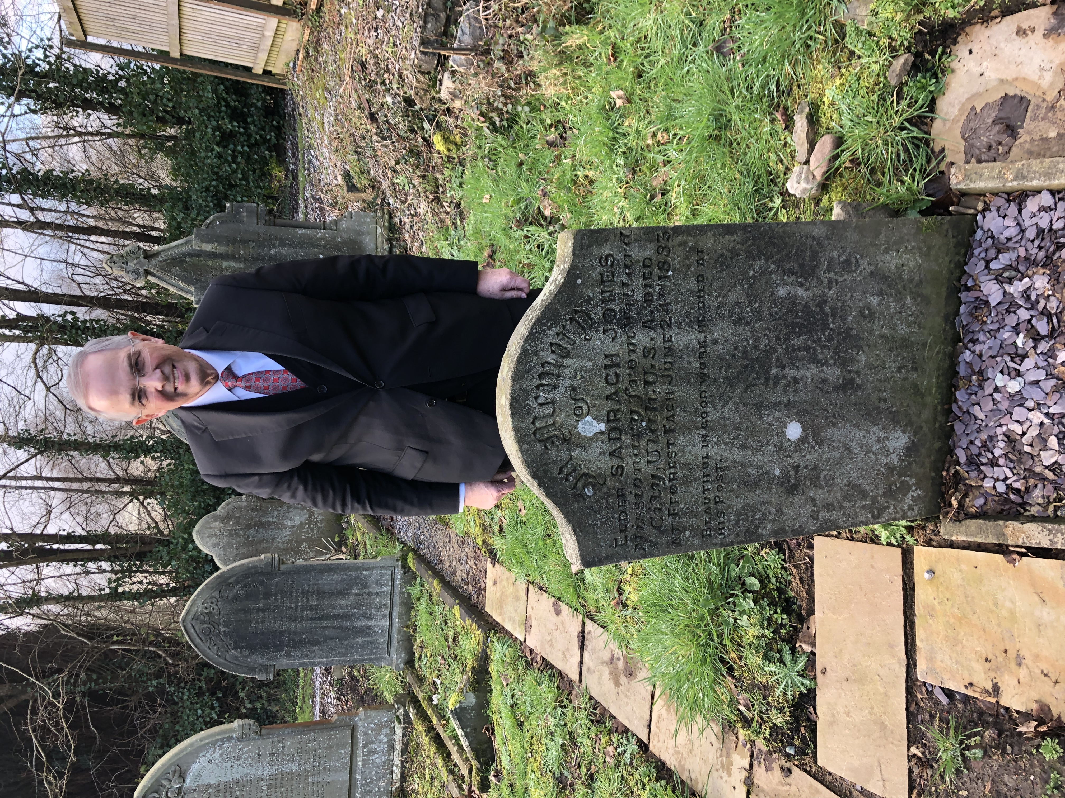 Elder Neil L. Andersen standing at the gravesite of Elder Sadrach Jones, a young man who emigrated to the United States and returned later to Wales as a missionary of the Church. He died while still a missionary in Wales in 1883.