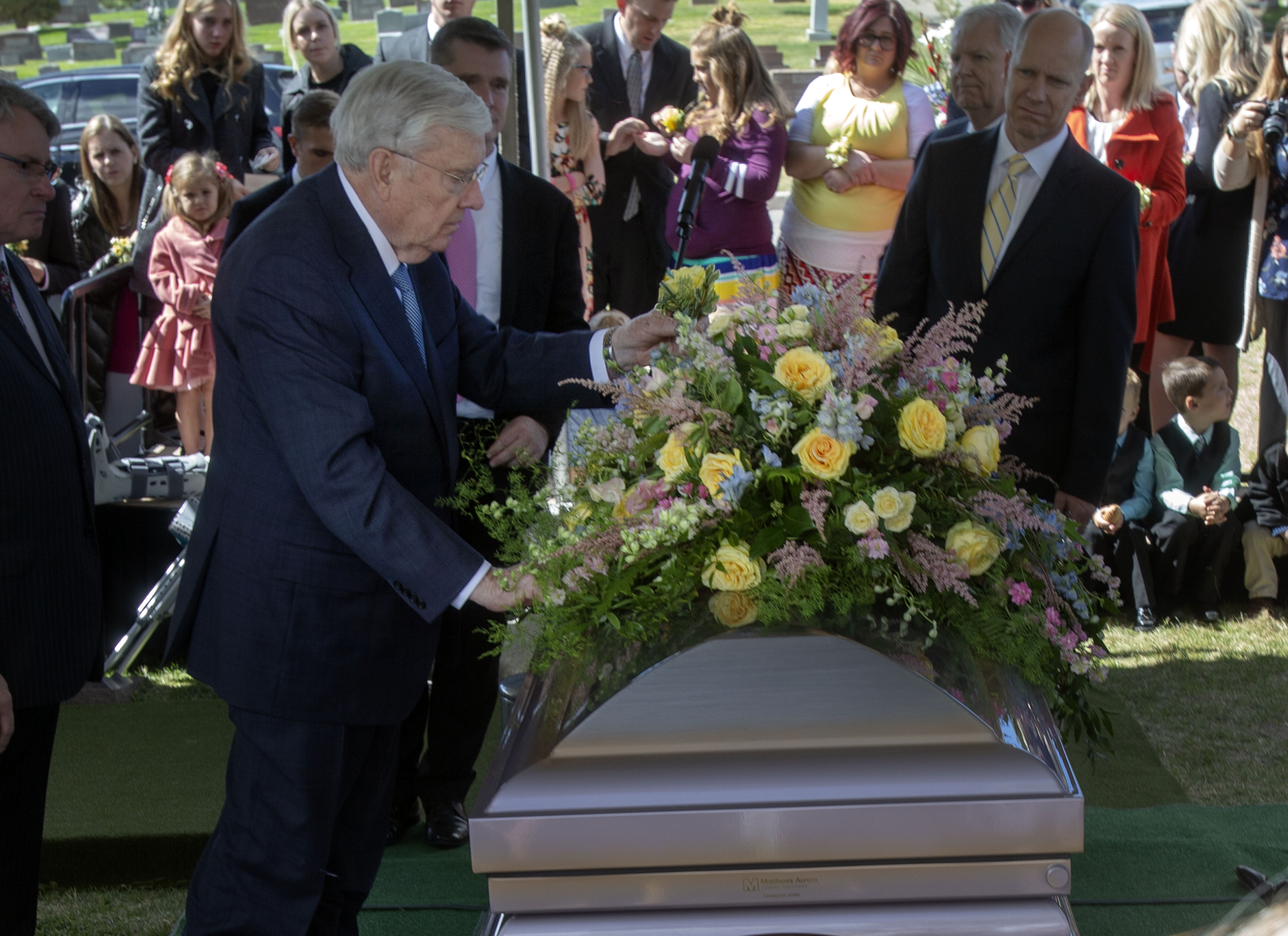 President M. Russell Ballard, acting president of the Quorum of the Twelve Apostles, places a yellow rose in the casket spray for his wife, Sister Barbara Ballard, who was laid to rest in the Salt Lake City Cemetery, Monday, October 8. 2018.