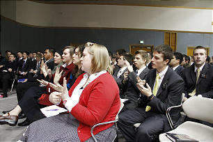 Missionaries at devotional use sign language while singing opening hymn.