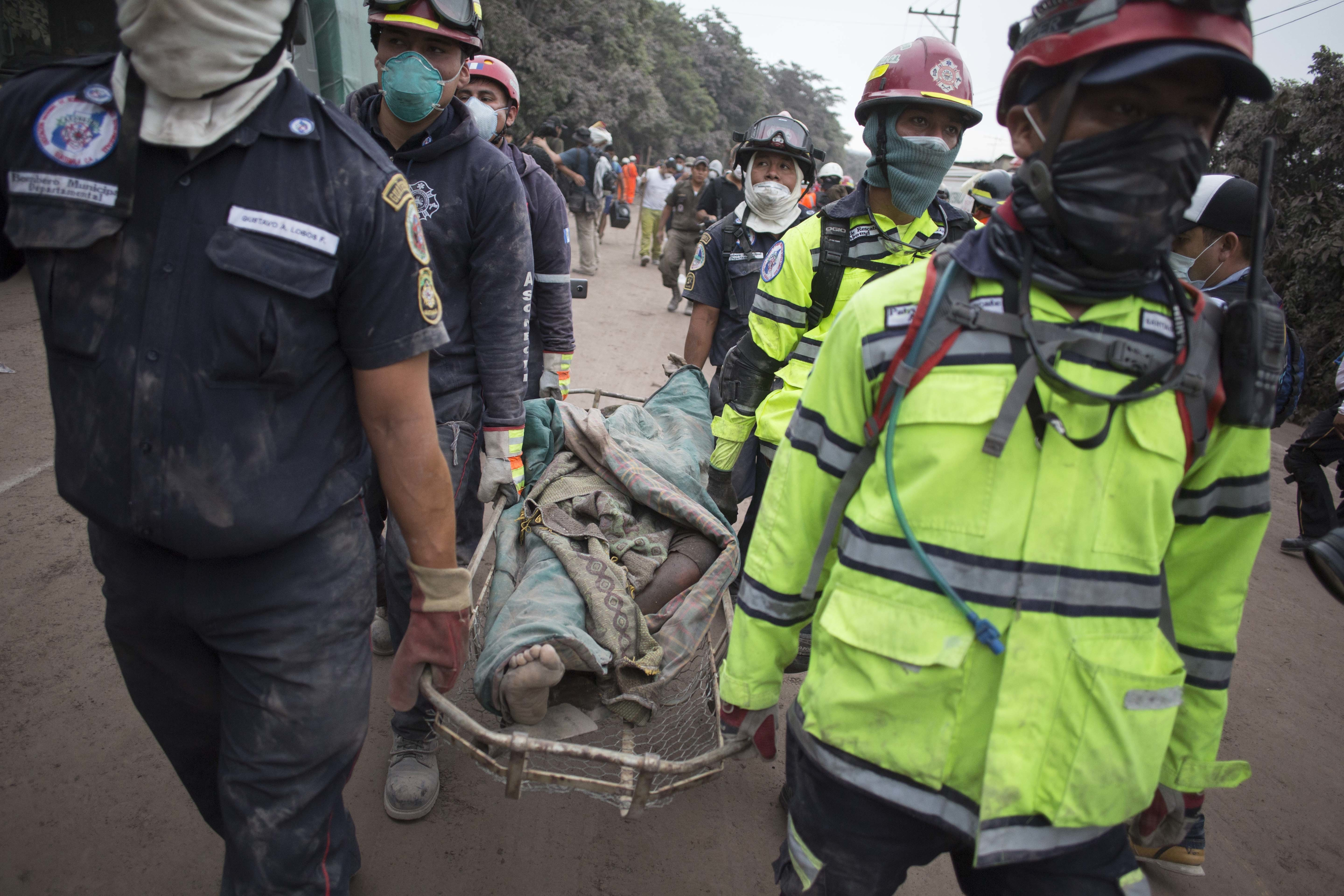 """Firefighters carry a body recovered near the Volcan de Fuego, or """"Volcano of Fire,"""" in Escuintla, Guatemala, Monday, June 4, 2018."""