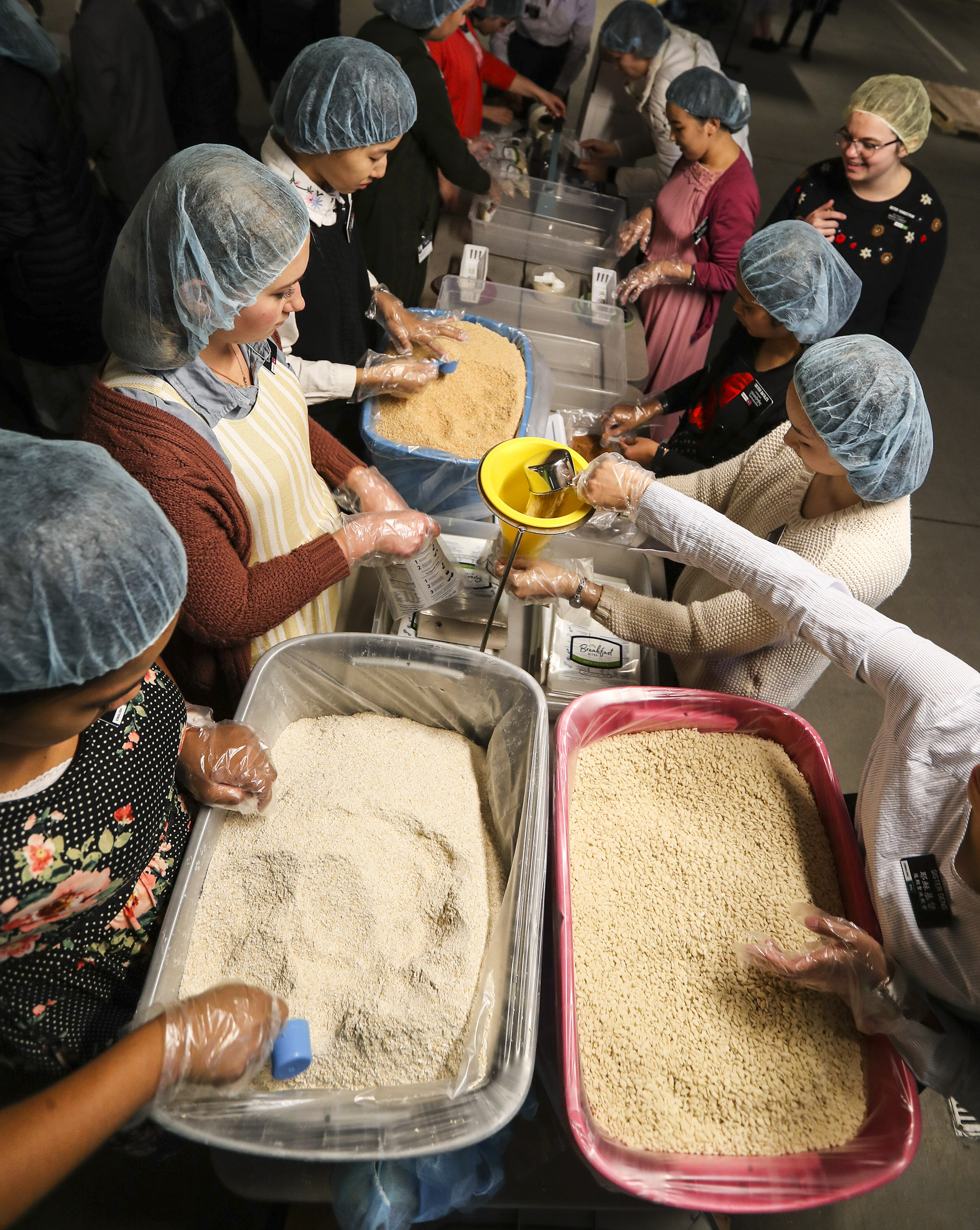 """Missionaries at the Missionary Training Center in Provo work to fill bags of """"Apple Pie Oats"""" as they participate in an annual service project with Feeding Children Everywhere to address the issue of domestic hunger. Working in a covered parking garage at the MTC, the group assembled more than 350,000 meals for the Utah Food Bank on Thursday, Nov. 22, 2018."""