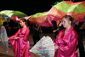 Mandee Quist, left, and Emily James participate in Chinese dance with parasols.