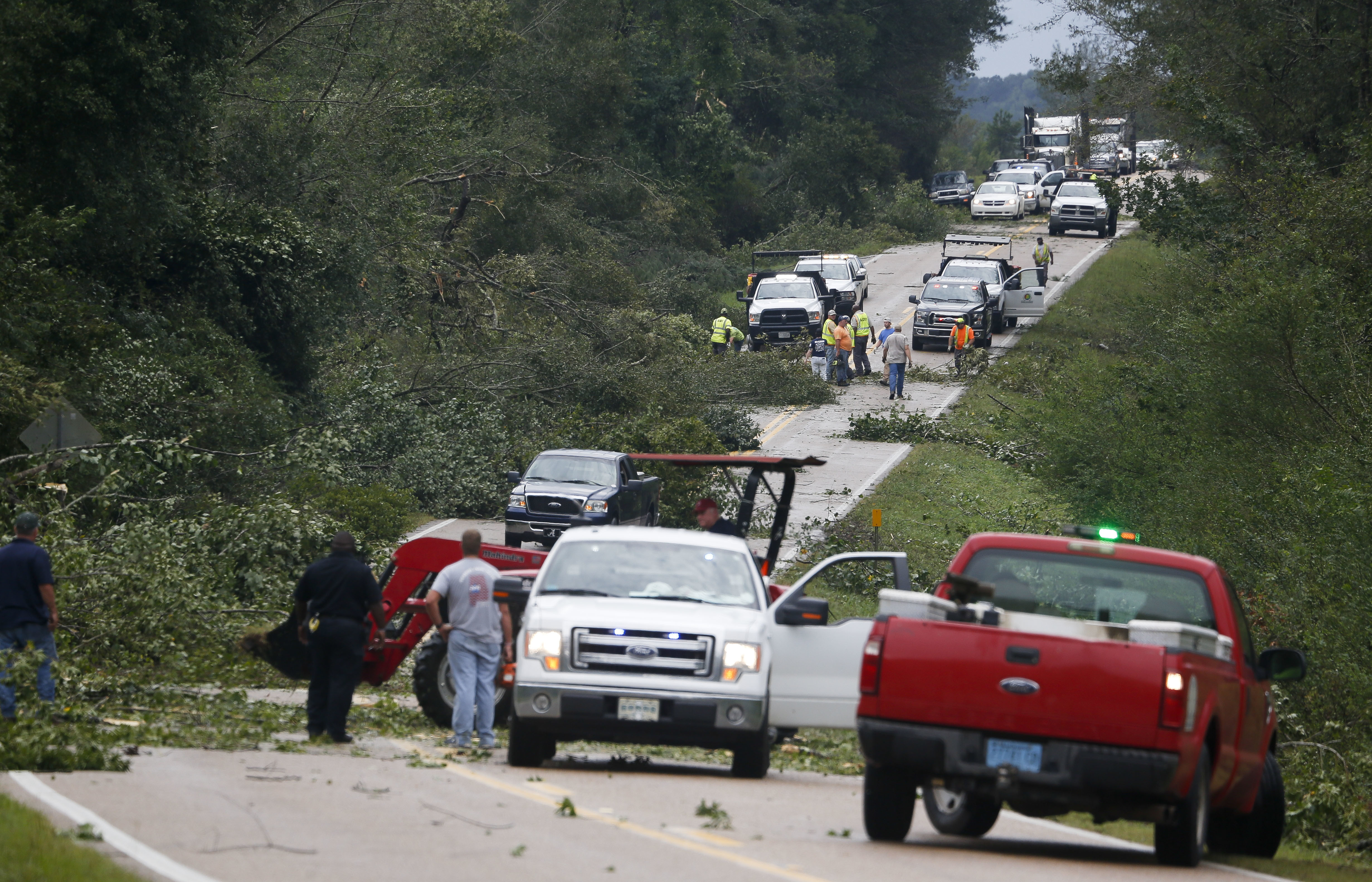 Volunteer firefighters work to clear Highway 17 in Pickens County, Ala., after a tornado struck Thursday, Aug. 31, 2017. The tornado damaged several homes in northwest Alabama as the remnants of Hurricane Harvey came through the state. (Gary Cosby Jr./The Tuscaloosa News via AP)
