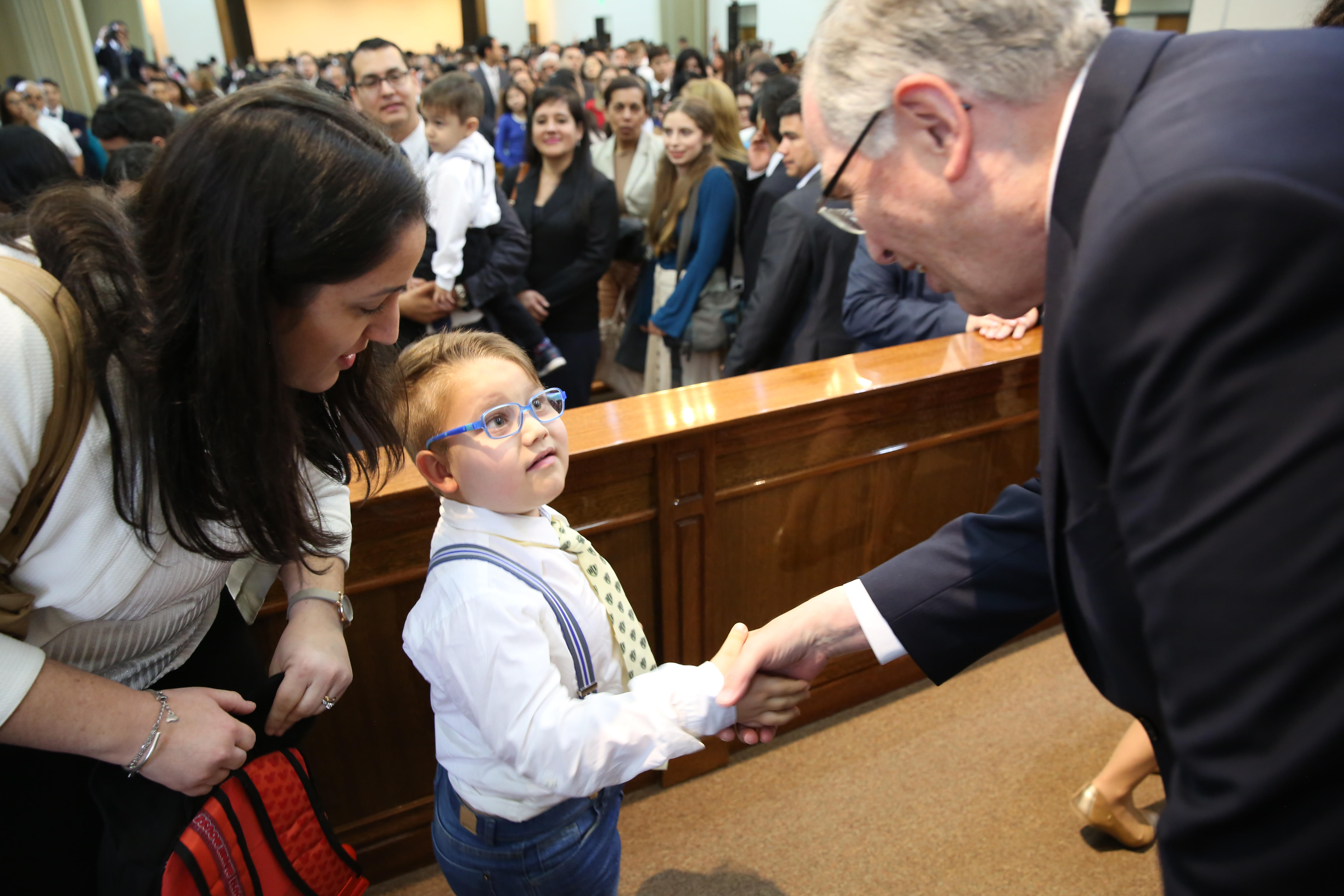 Elder Neil L. Andersen shakes hands with a young boy following a stake meeting in Resistencia, Argentina, in April 2019.