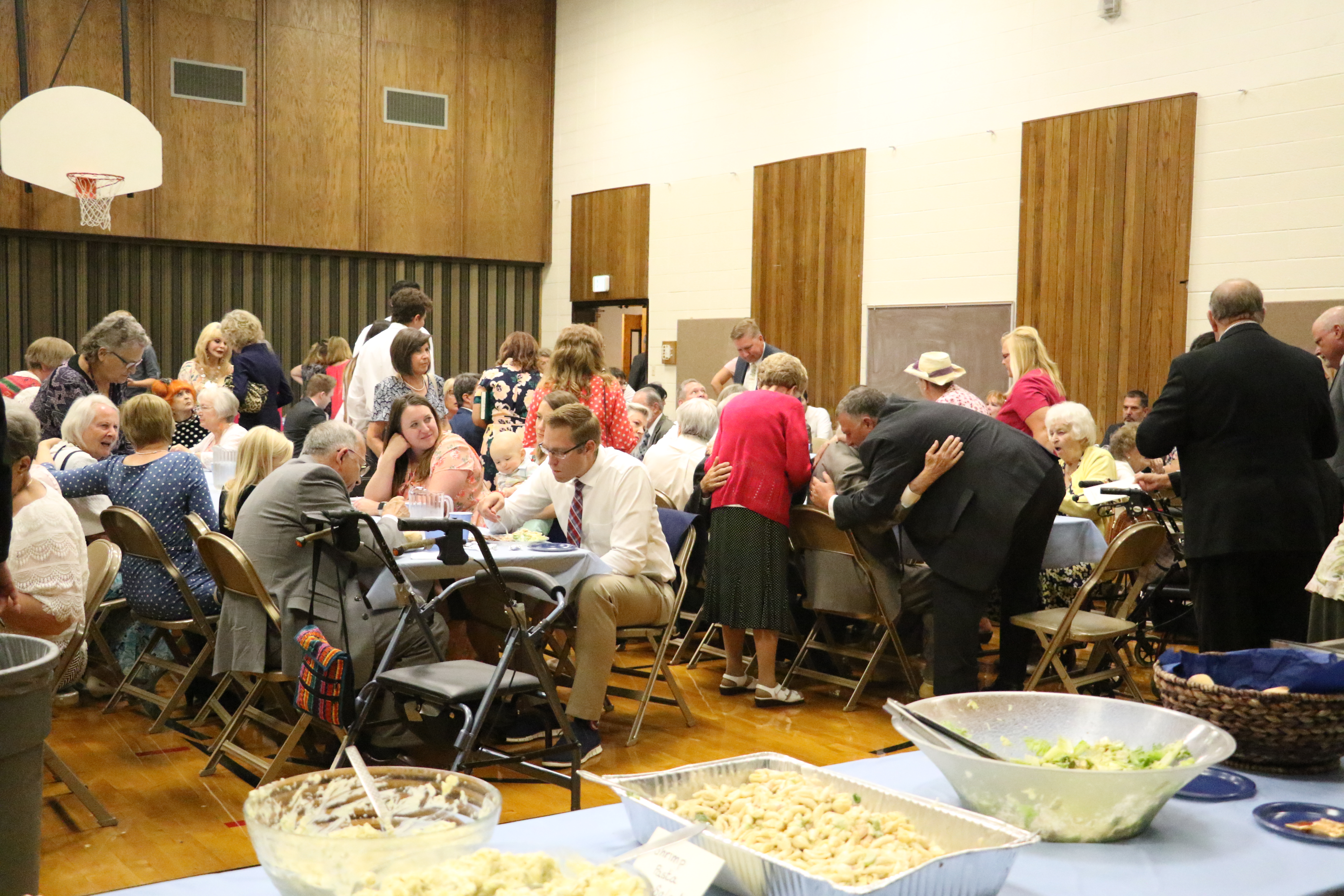 Family and friends gather in the cultural hall to enjoy food and each other's company after the German Speaking Ward's final sacrament meeting on July 14, 2019.