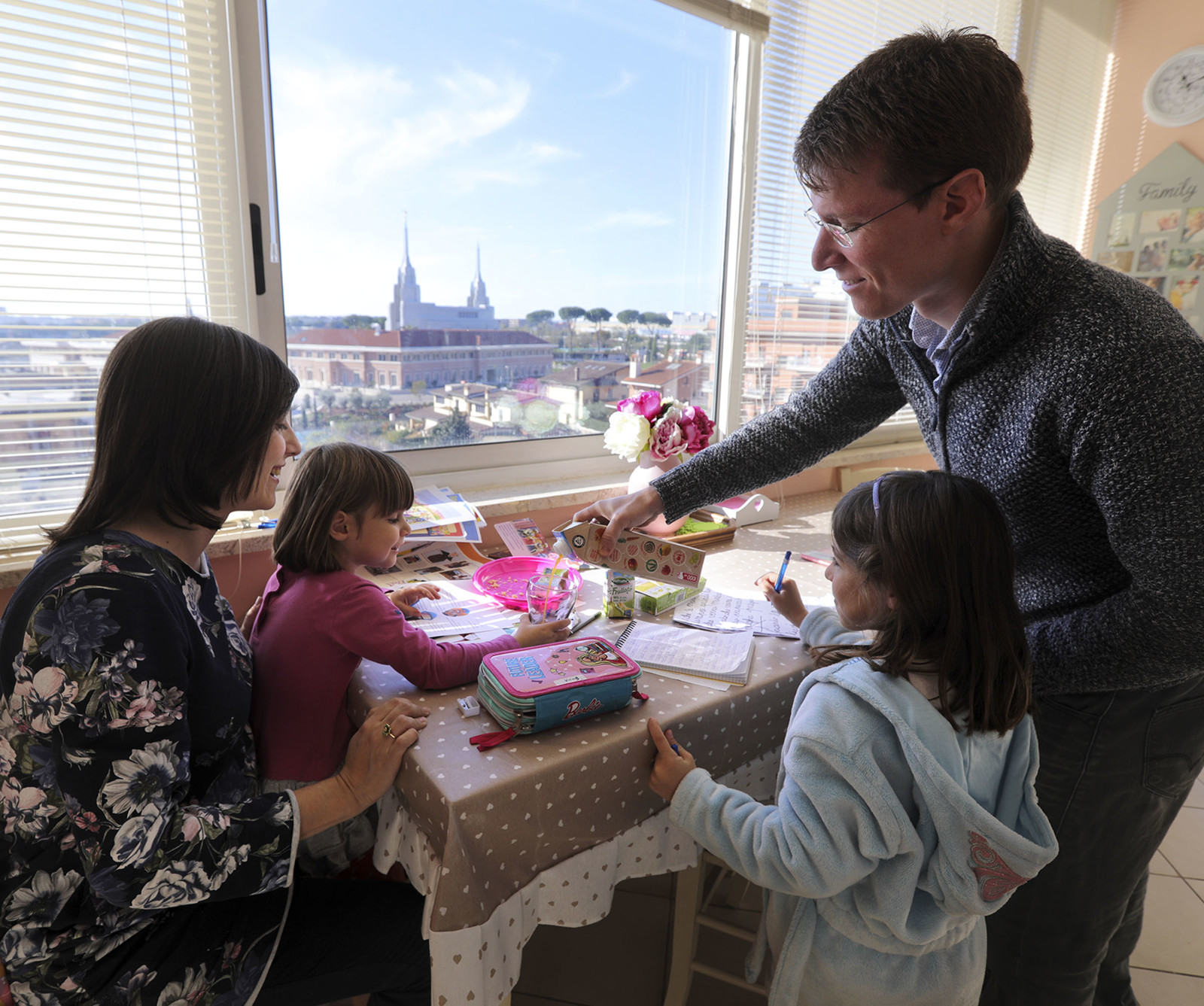 The Salerno Family eating breakfast as the Rome Italy Temple shows through their kitchen window.