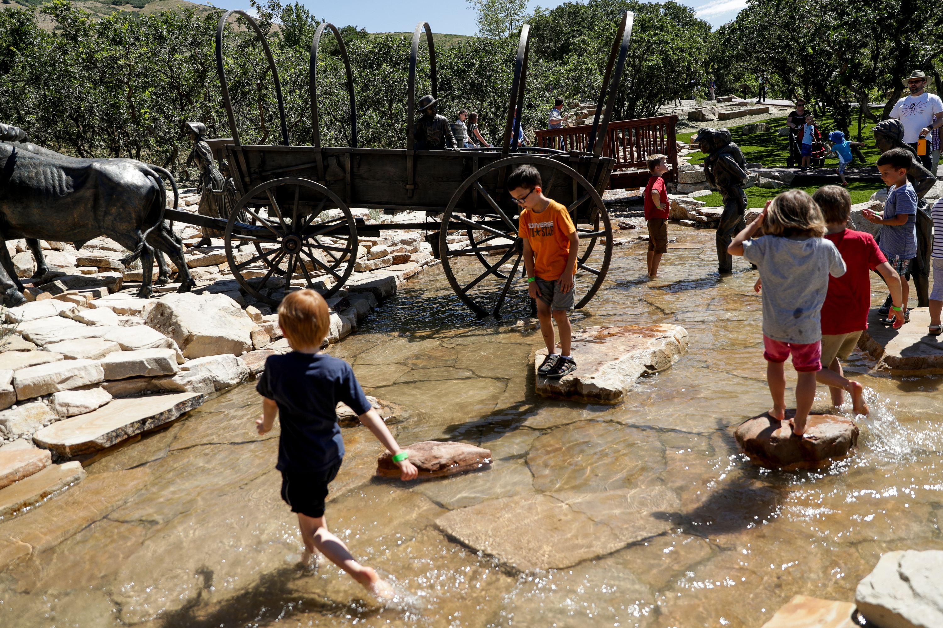 Children play in a steam at the Children's Pioneer Memorial at This Is the Place Heritage Park in Salt Lake City on the day of the memorial's dedication, Saturday, July 20, 2019.