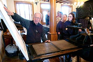Elder Harold Dance explains to visitors at the printing office how the newspaper was produced.