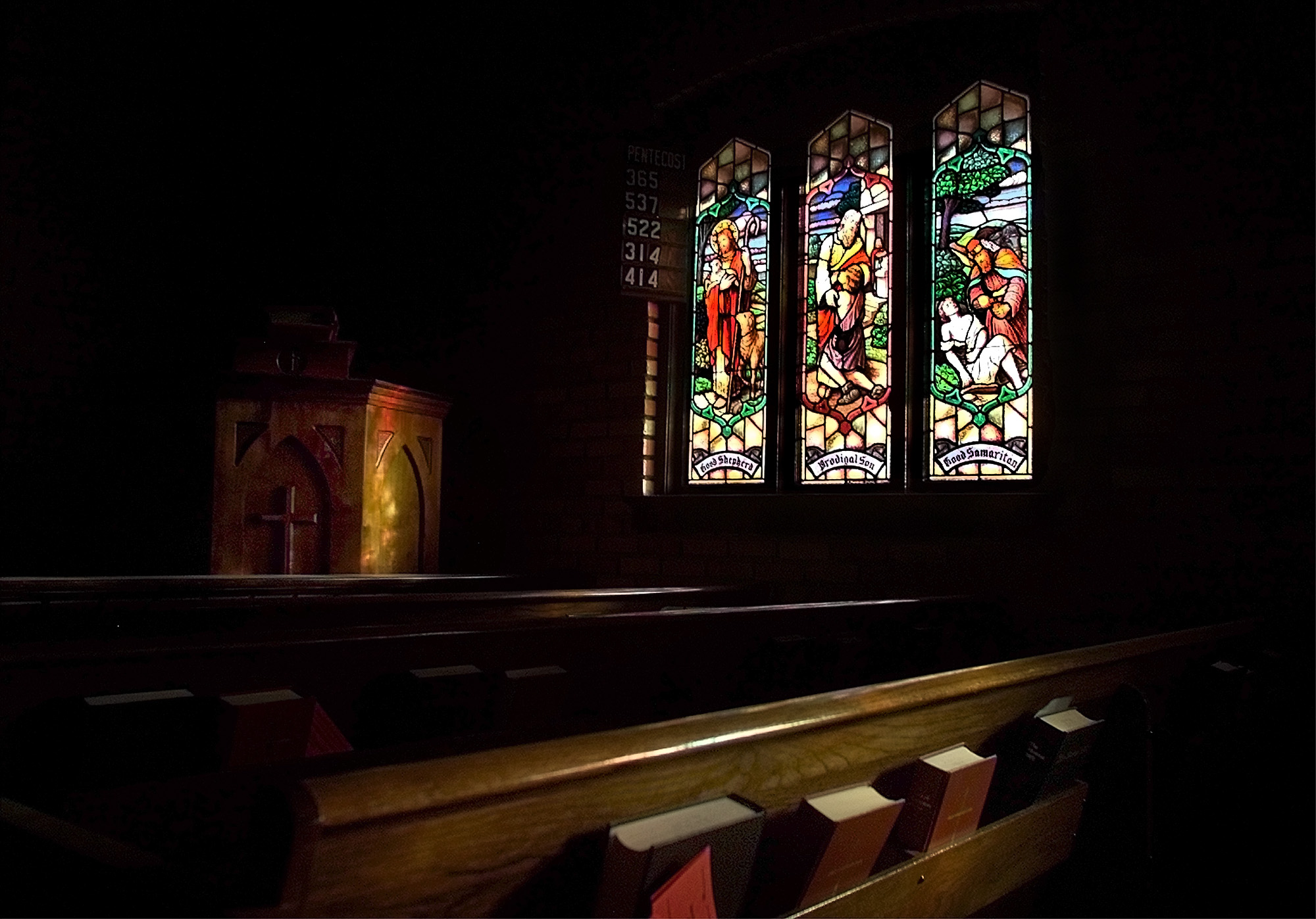 Stained glass windows in the chapel at St. Mary's Episcopal Church in Provo illuminate the podium and pews. The window seen depicts the Good Shepherd, Prodigal Son and Good Samaritan.