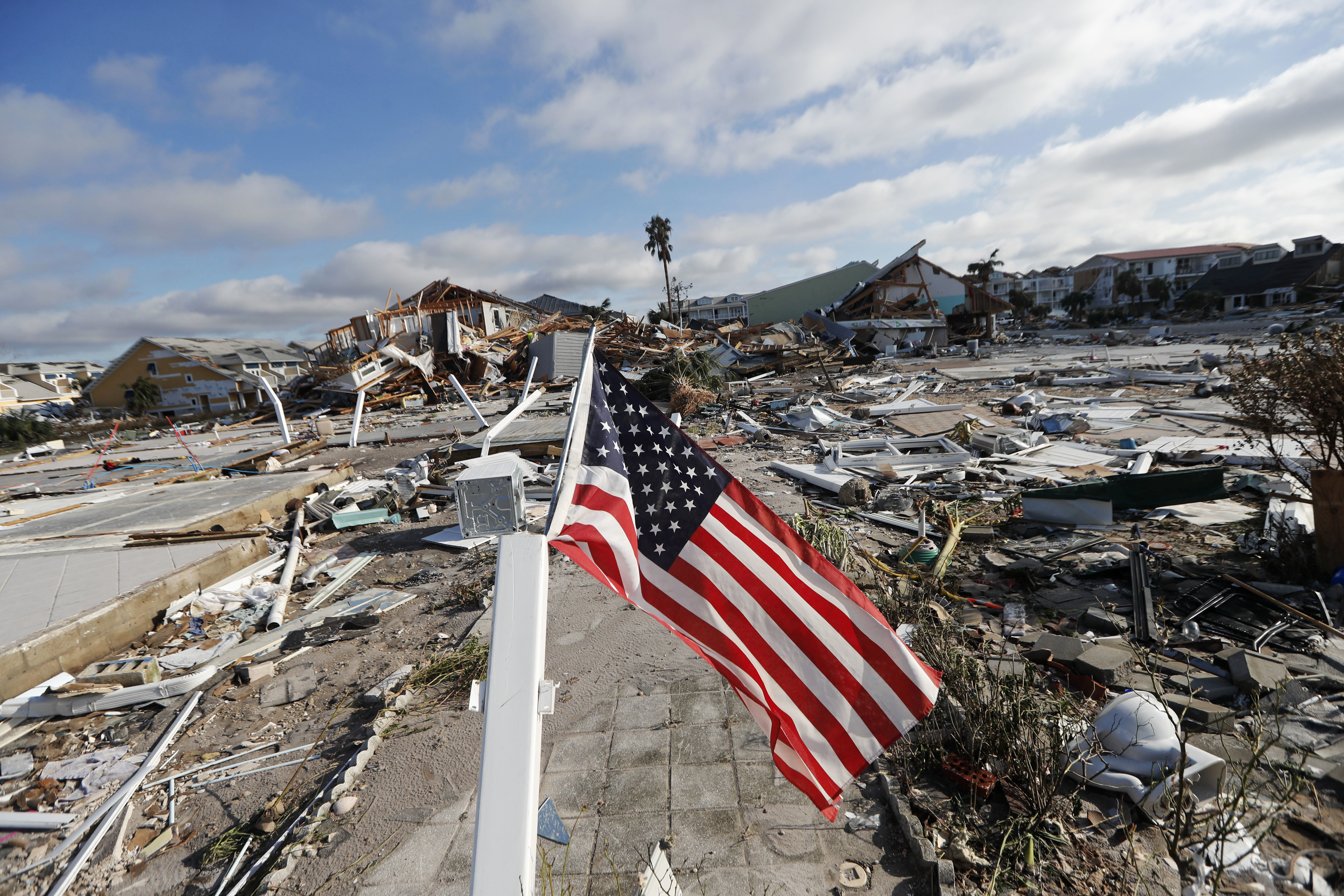 An American flag flies amidst destruction in the aftermath of Hurricane Michael in Mexico Beach, Fla., Thursday, Oct. 11, 2018.