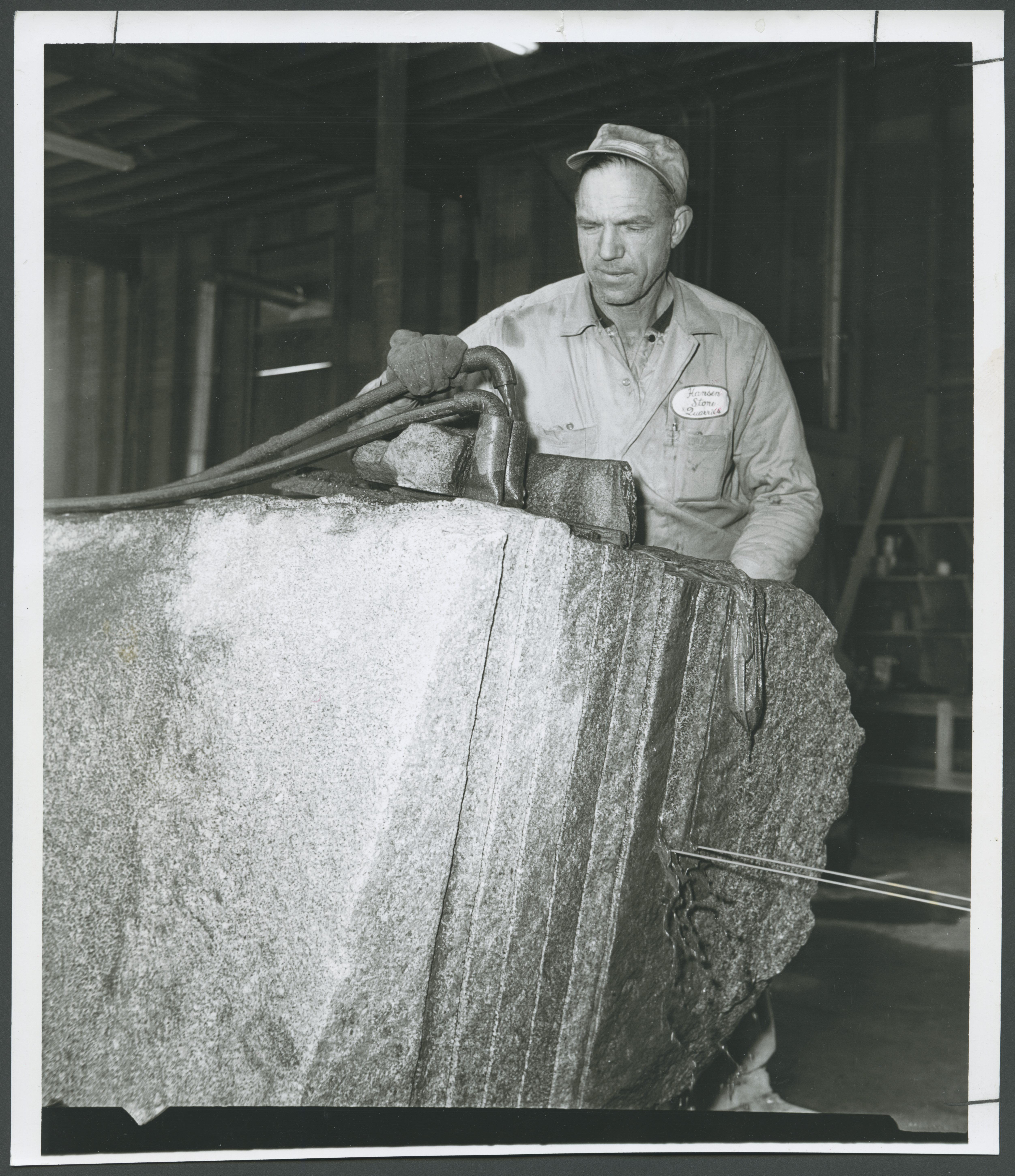 Wilford Hansen checks the water being used in cutting huge piece of granite for temple projects on Jan. 28, 1963. Saw is at lower right.