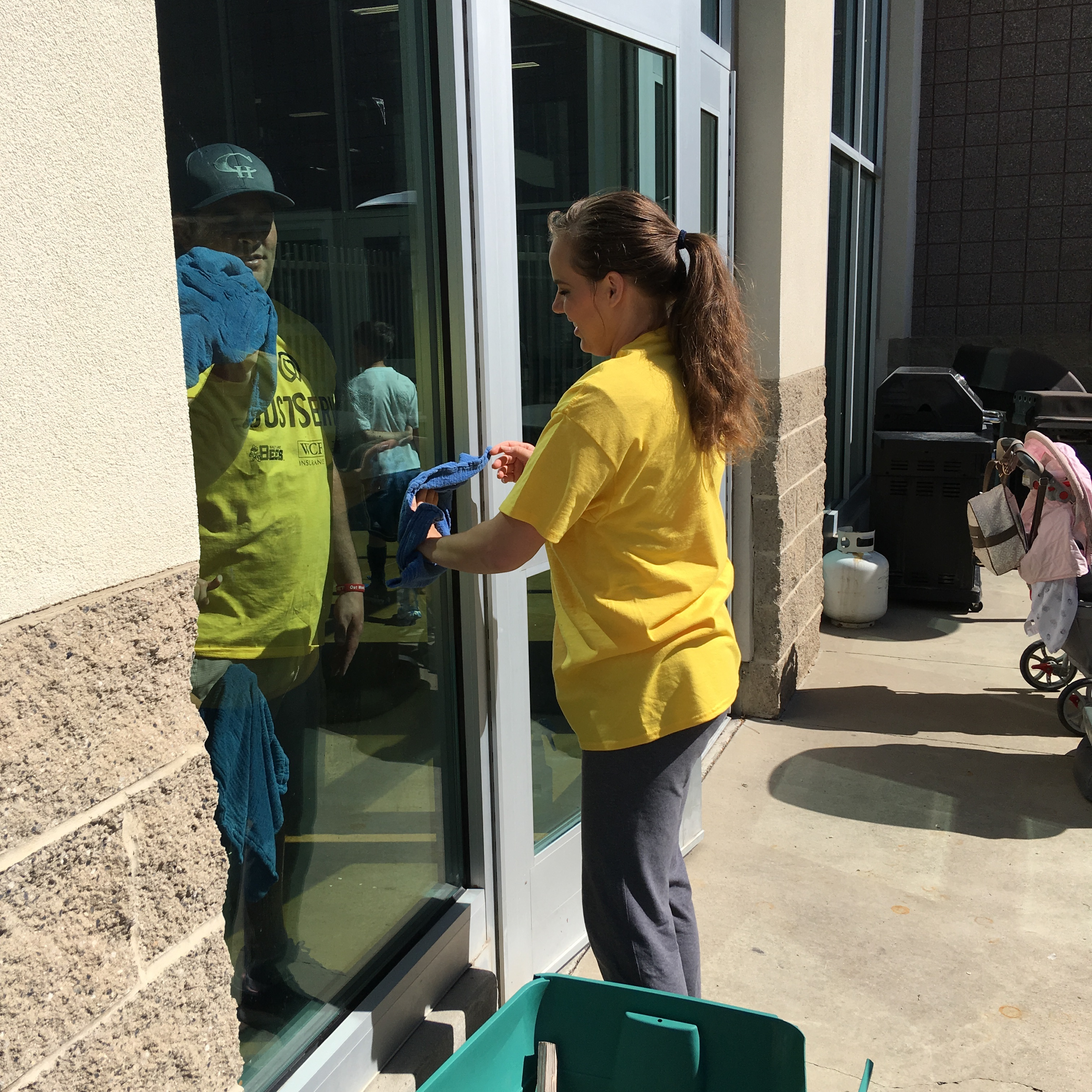 JustServe volunteers clean windows at Centennial Park in West Valley City as part of the Salt Lake Bees/JustServe day of service on April 27.
