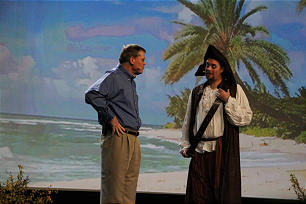 """Elder Dennis C. Brimhall, CEO of FamilySearch International and an Area Seventy of the Church, speaks with pirate """"Jack Starling"""" during his address at keynote session of RootsTech 2014 Feb. 6. The pirate helped introduce a new volunteer indexing initiative of newspaper obituaries: """"Dead men tell no tales -- but their obituaries do!"""""""