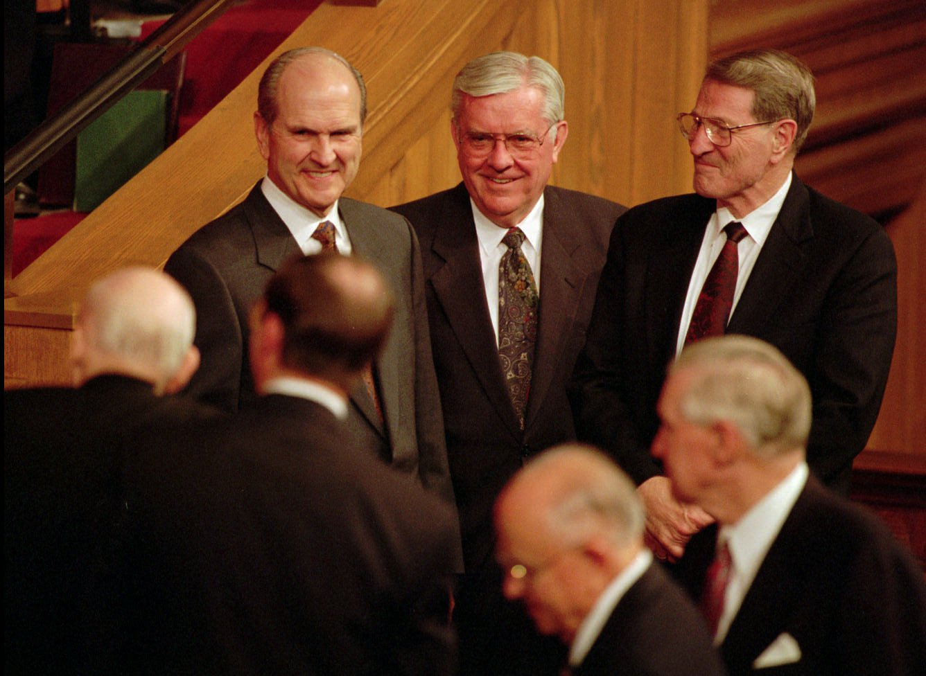 Elder Russell M. Nelson, Elder M. Russell Ballard and Elder Neal A. Maxwell, all of the Quorum of the Twelve Apostles, watch with smiling faces as President Howard W. Hunter makes his way out at the end of conference.