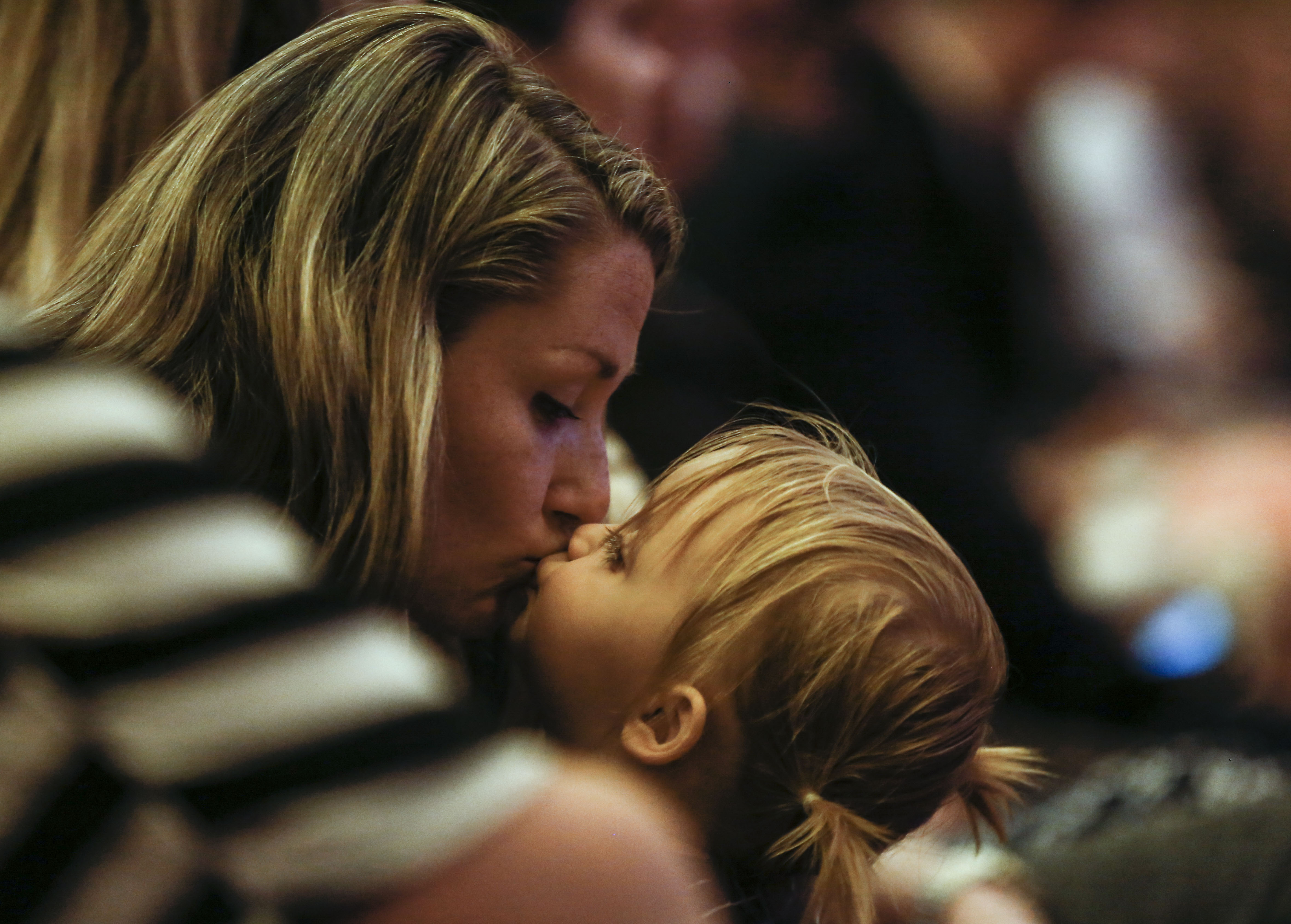 Jessica Chambers gives a kiss to her daughter Maggie, 1, during the Worldwide Devotional for Young Adults at the Salt Lake Tabernacle in Salt Lake City on Sunday, May 5, 2019.
