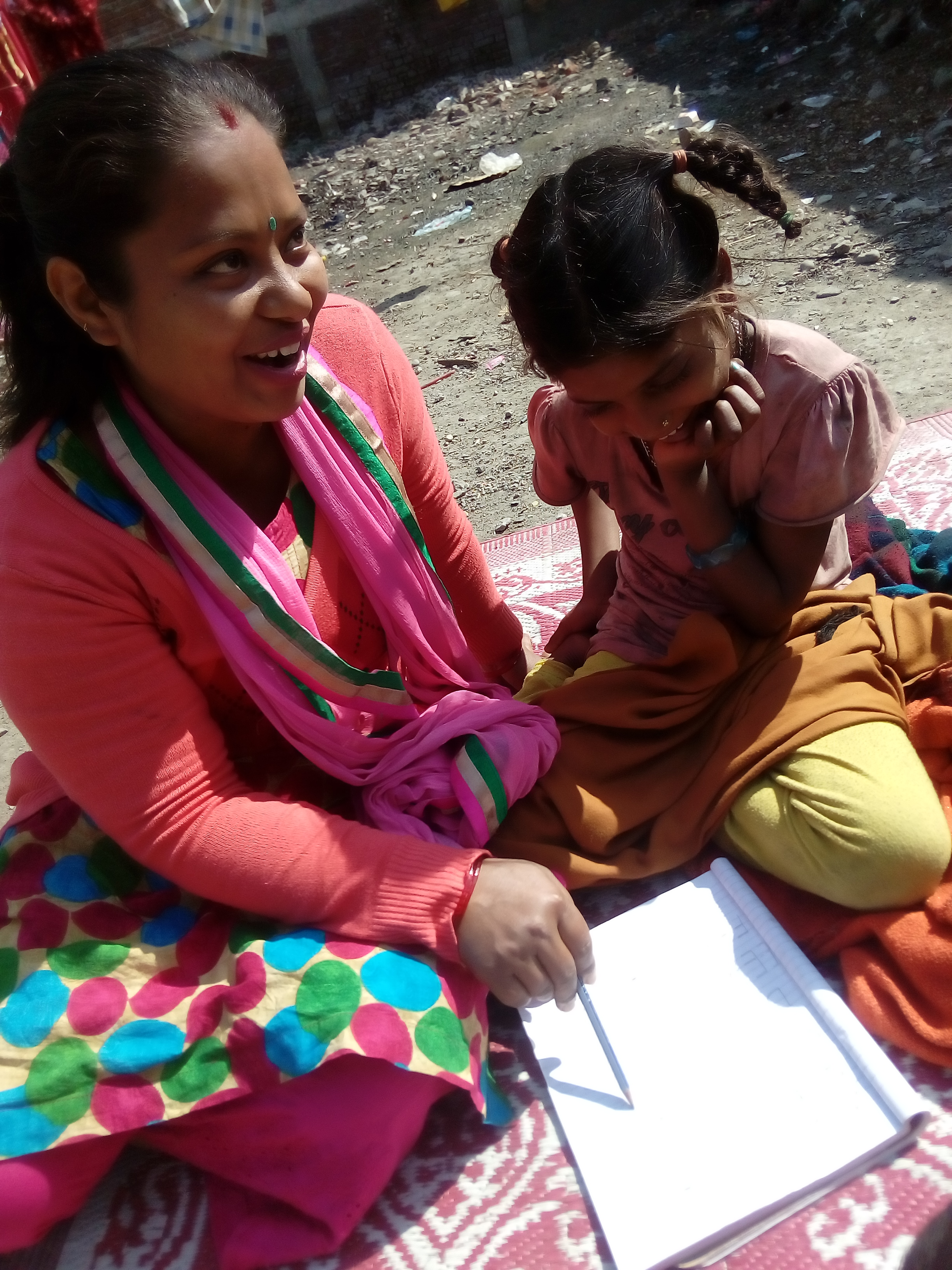 """Students in Nepal learn while sitting on blankets in an """"open air classroom."""""""