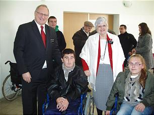 Elder and Sister Juncker pose with wheelchair recipient in Kosovo.