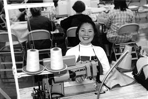 Kim Enciso of the Portland Oregon Stake flashes a smile while working during service project. She and husband, Julio, professional tailors and converts to the Church, donated the use of their own industrial sewing machines and sergers.