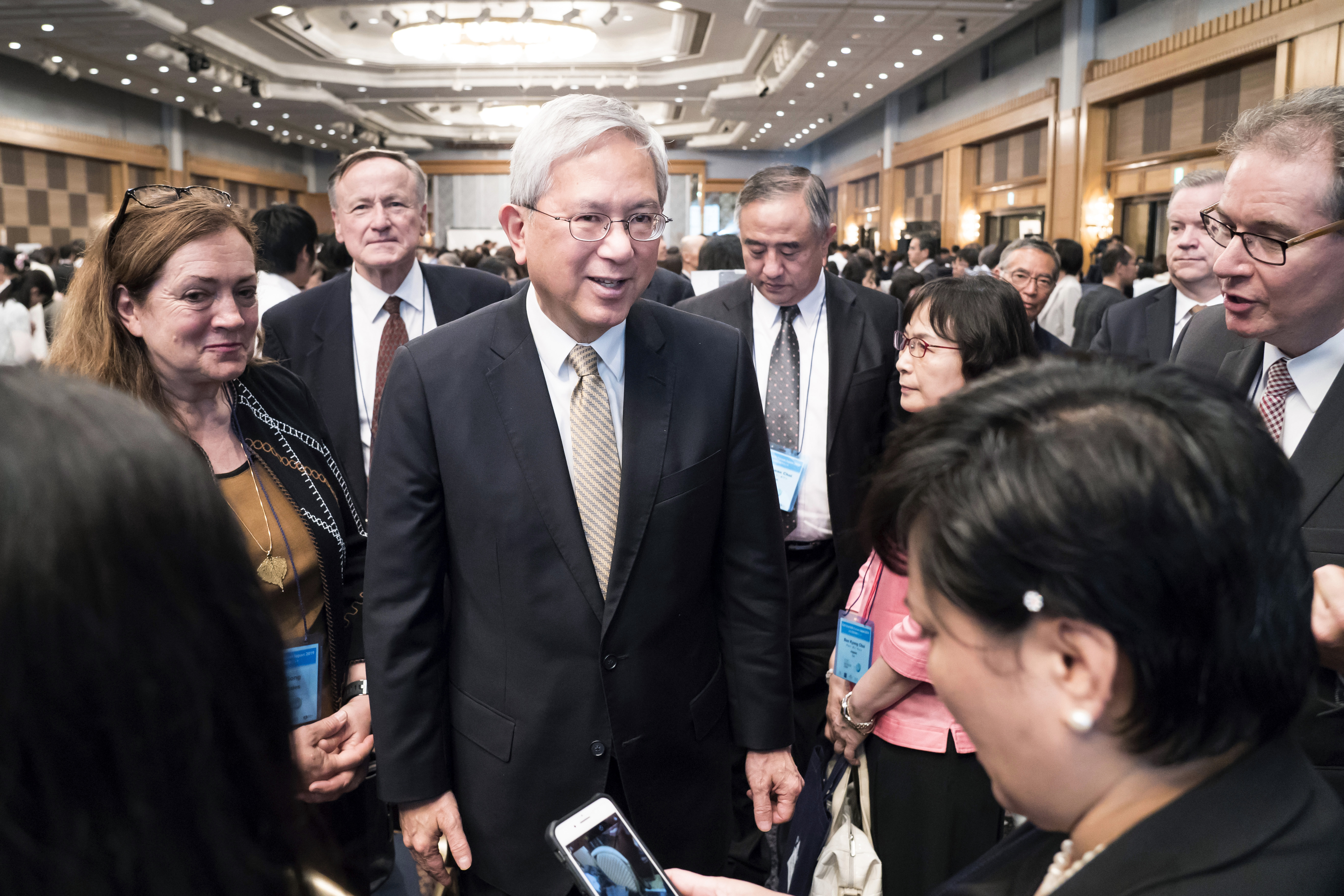 Elder Gerrit W. Gong of the Quorum of the Twelve Apostles of The Church of Jesus Christ of Latter-day Saints, center left, is surrounded by attendees after a session during the G20 Interfaith Forum in Chiba, Japan, on Saturday, June 8, 2019.