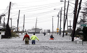People wade and paddle down a flooded street as Hurricane Sandy approaches, Monday, Oct. 29, 2012, in Lindenhurst, N.Y.