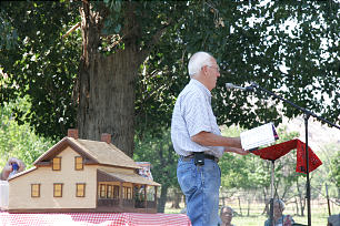 Standing next to a model of the Alonzo and Nancy Russell Home, historian Ronald L. Morris addresses the audience at the Grafton reunion on Sept. 26.