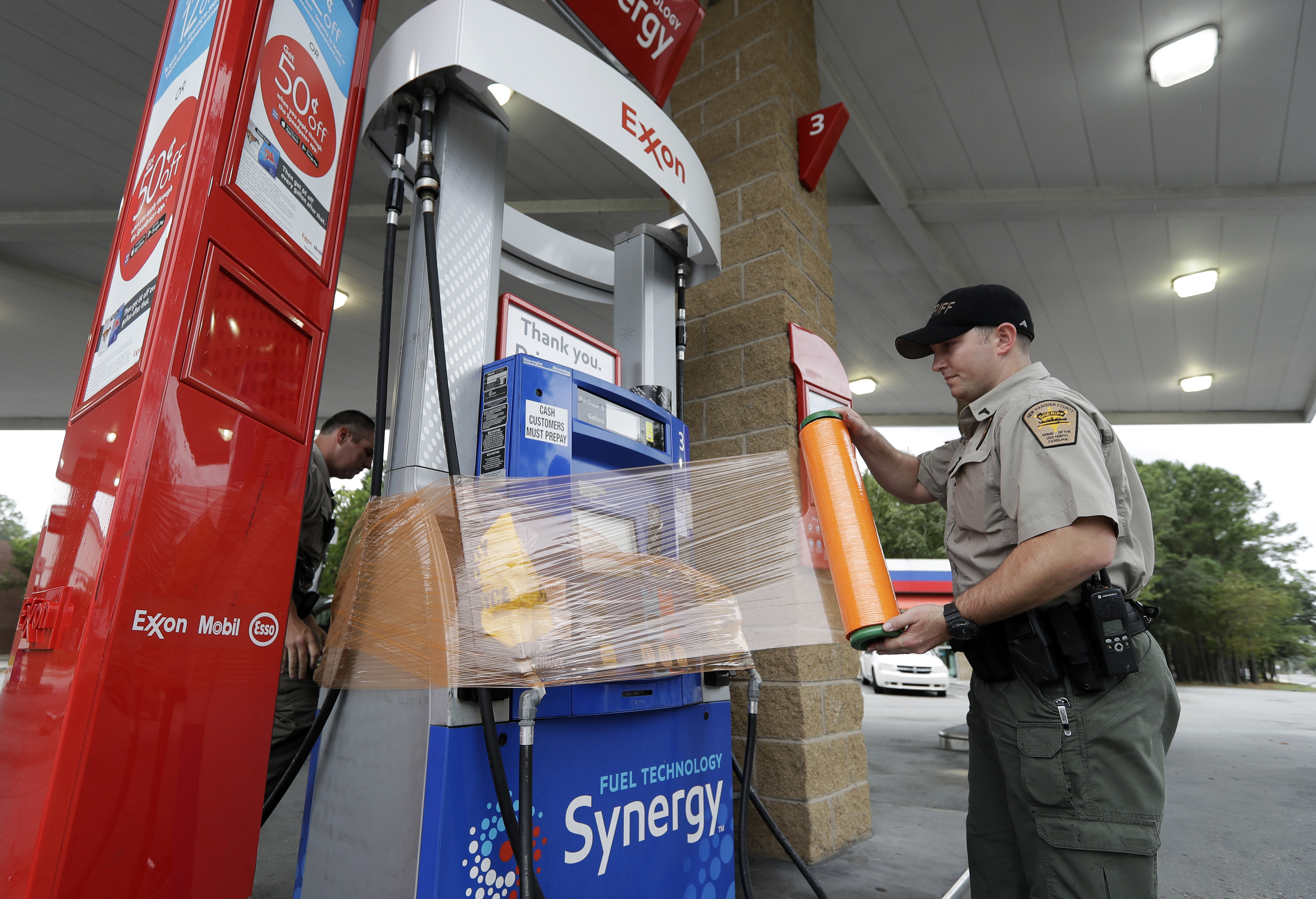 New Hanover Sheriff's Corp. N. Brothers wraps a gas pump for protection in Wilmington, N.C., as Hurricane Florence threatens the coast Thursday, Sept. 13, 2018.