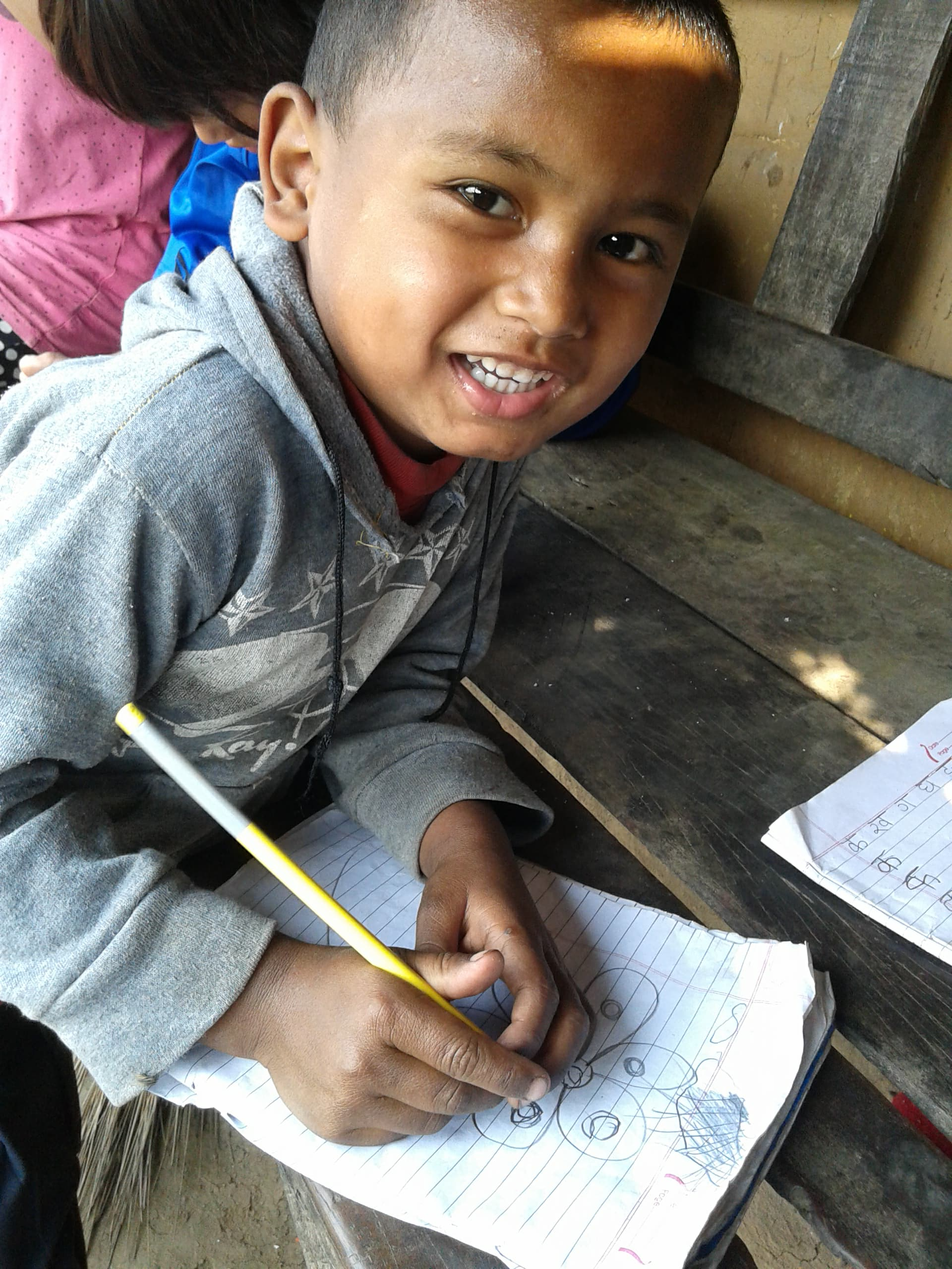 A young boy in Nepal learns in an open air classroom. Although most of the students in the slums are girls, Maharjan says they are working to help young boys stay interested in education.
