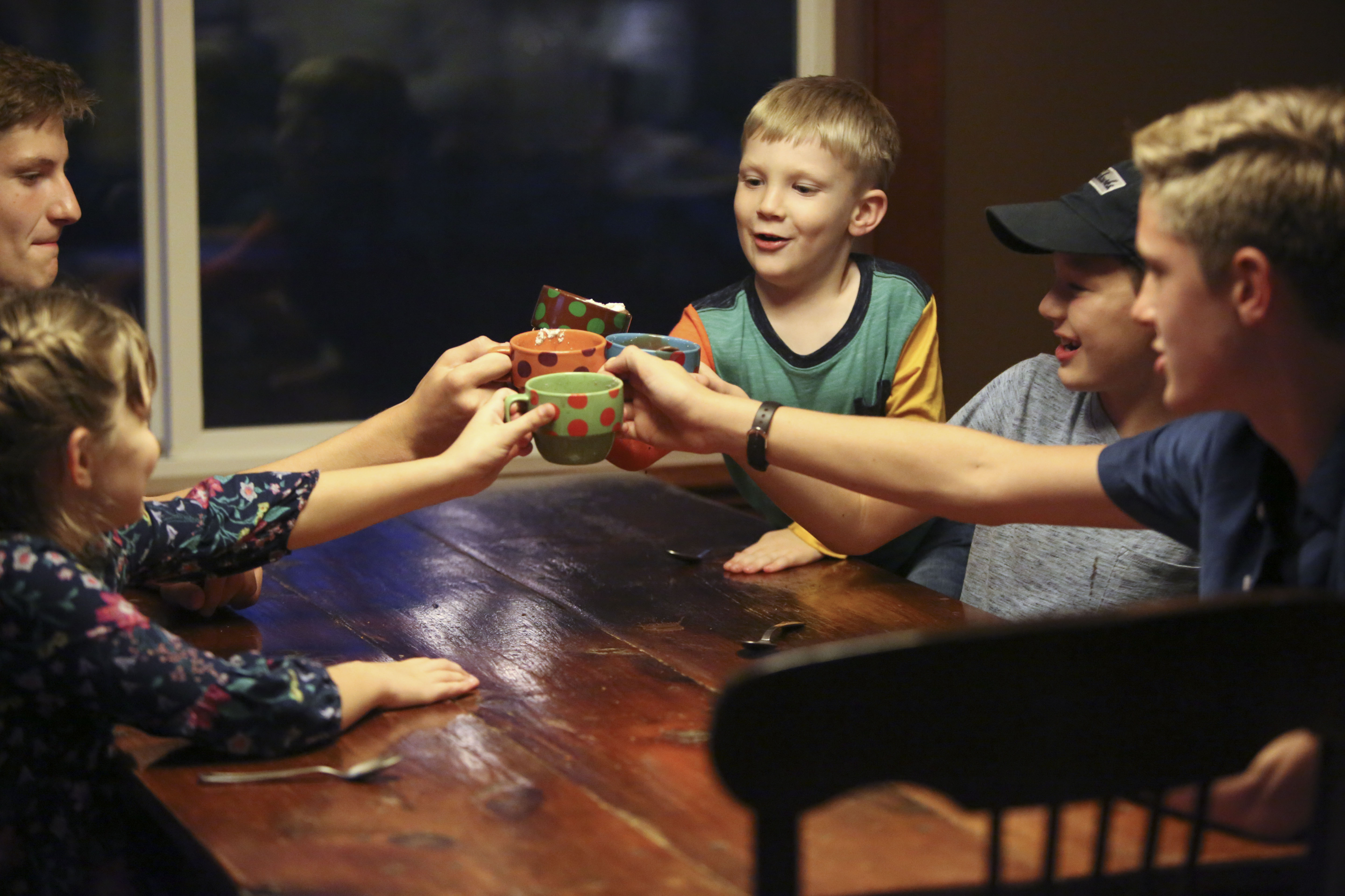 Emilia, Ben, Daniel, Tom and Jonathan Allen cheers with hot chocolate mugs after getting caught in a rain storm at home in Renton, Wash., on Friday, Sept. 14, 2018.
